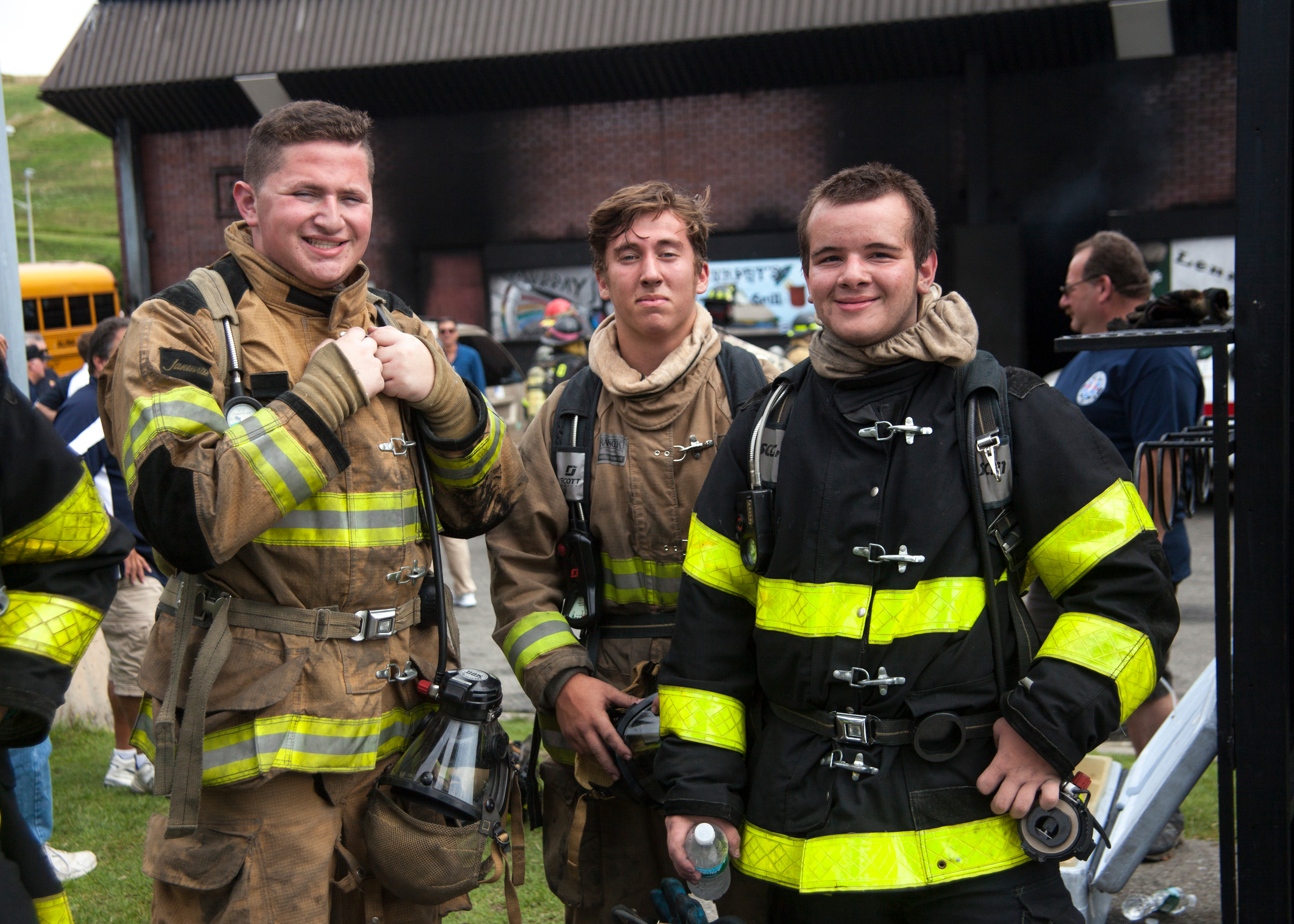 Jr Firefighters Mason Kletter of Glen Cove, Louis Sabatino of Franklin Square and Nicholas Capone of East Rockaway finished up the Warehouse fire exercise where the firefighters crawl into a burning warehouse at the facility fully outfitted in the same gear as actual fire fighters, including air tanks, and feel the heat and smoke before crawling out to take turns manning the hoses to extinguish the blaze.
