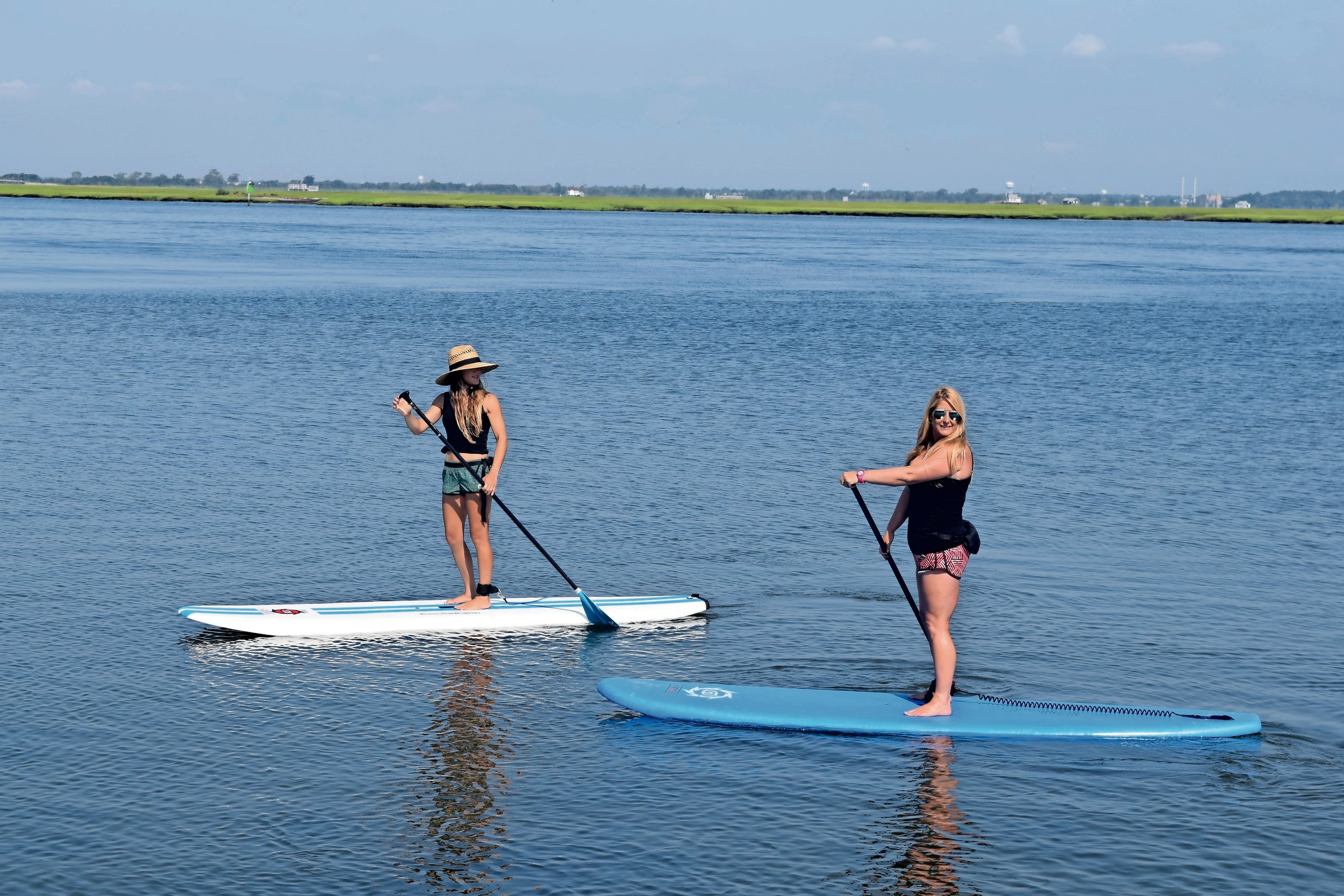 Jennifer Hanono, left, and Nicole Glasser paddled out at Jones Beach Field 10 to practice yoga.