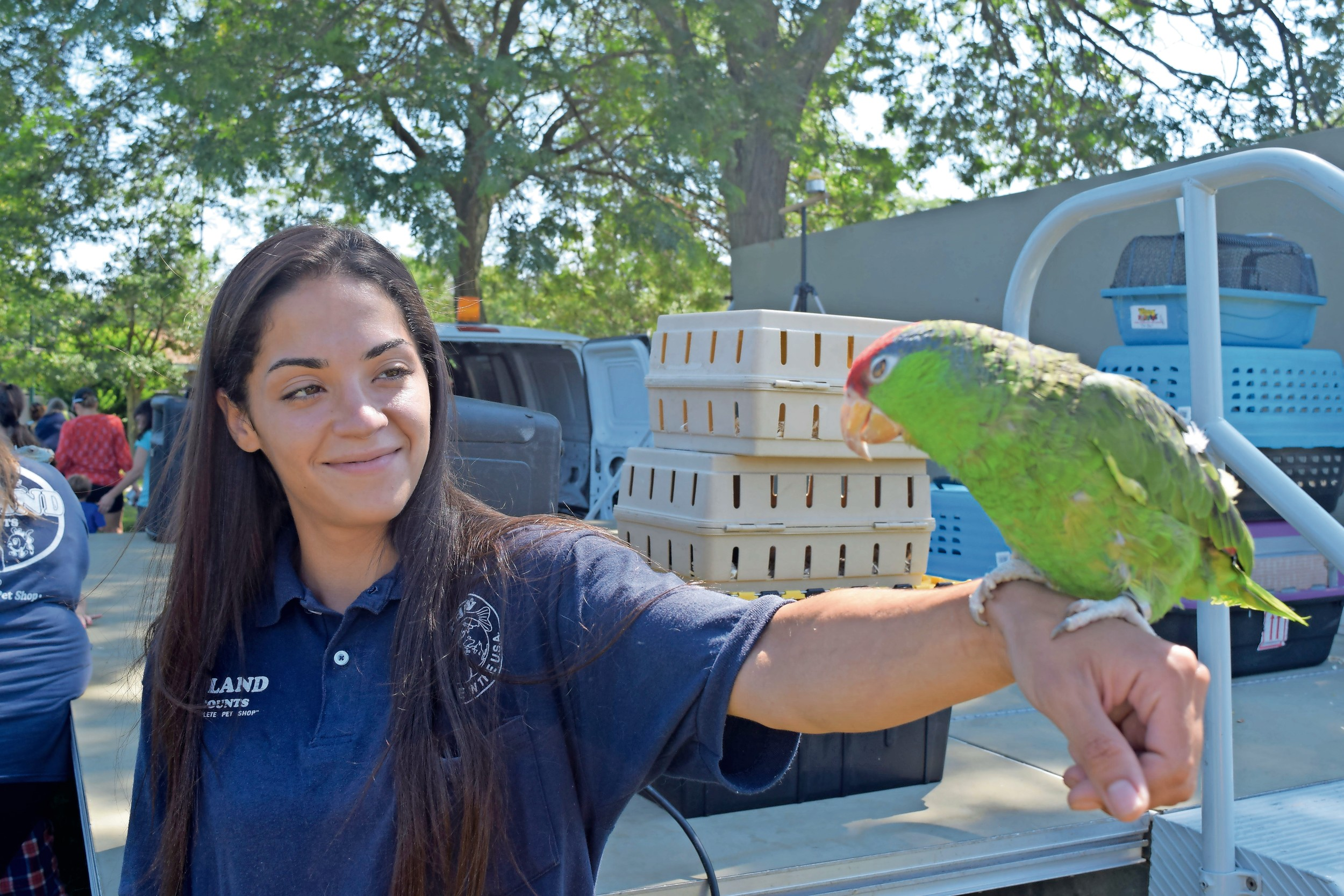 Allinna Comacho showed local children a tropical parrot to at the Town of Hempstead's Petland Parties program at Forest City Park on Aug. 1.