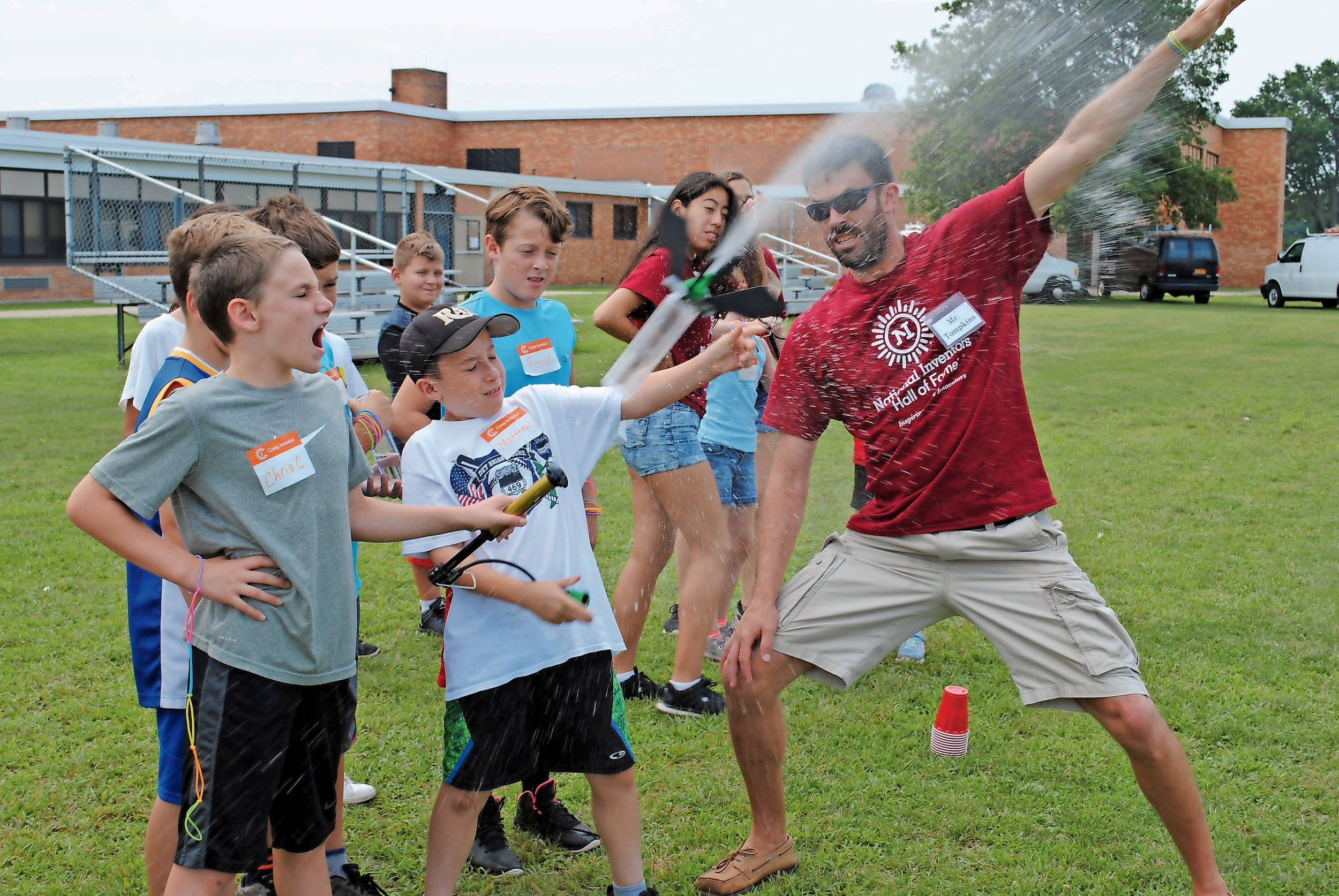 Eric Tompkins, a science teacher at MacArthur High School, helped Christopher Chianese, far left, and Matthew Hartmann launch water out of a rocket at Camp Invention, a hands-on summer science camp for students in the Levittown School District.