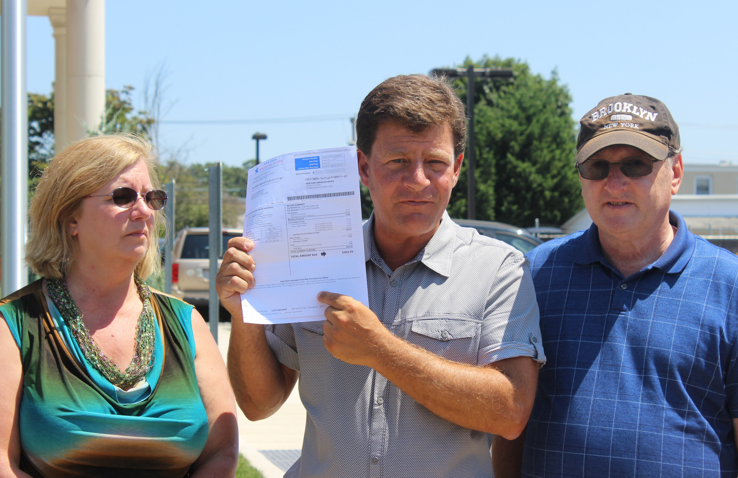 Long Island Clean Air Water and Soil co-director Dave Denenberg, center, showed the Herald his July water bill, half of which went to pay New York American Water's property taxes.