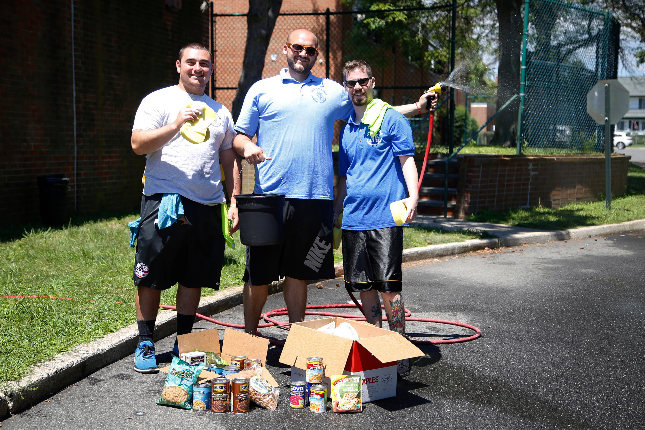 Coordinators Mike Kindin, left, Ryan Pearsall and Ryan Finn with some of the food donations they helped collect for the Oceanside Community Service food pantry at School No. 2's car wash on July 27.