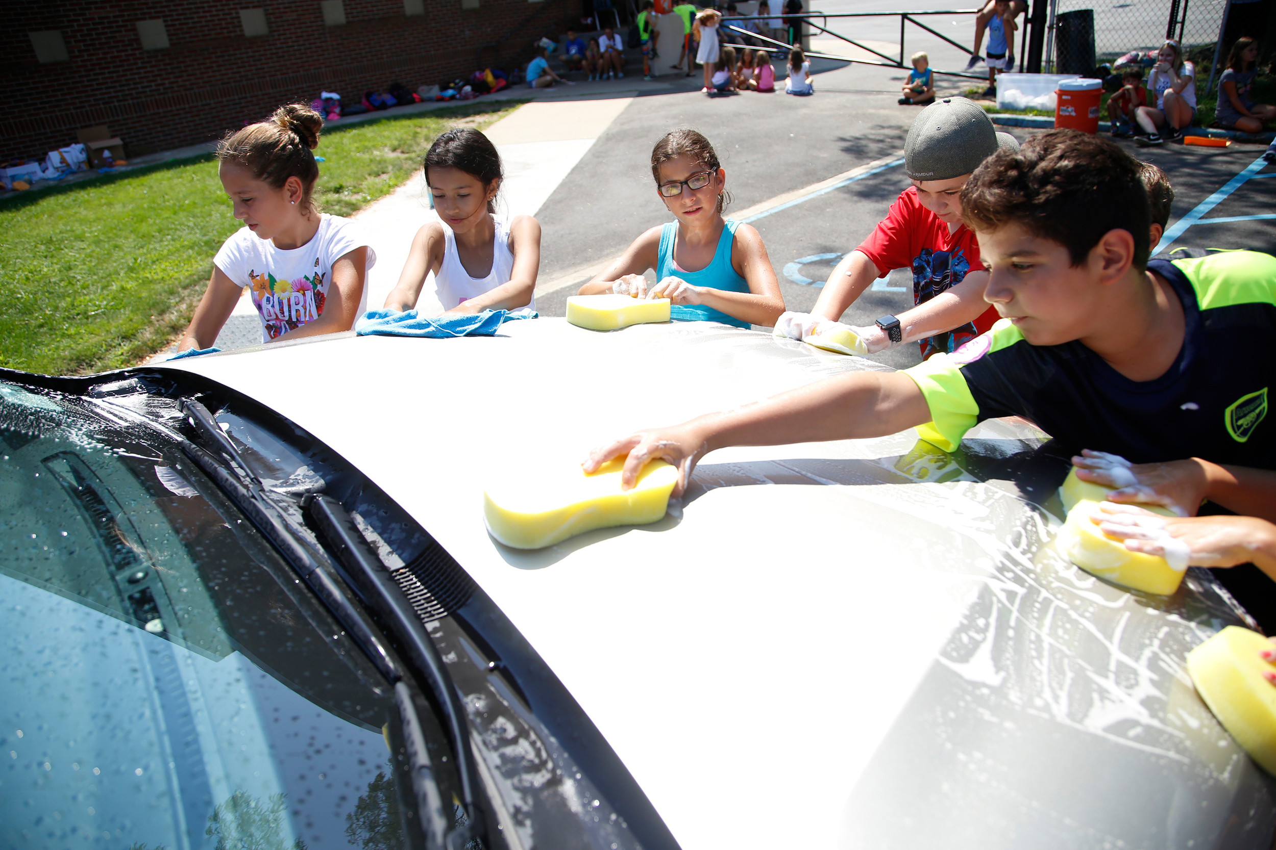 Kids from the School No. 8 summer recreation program clean a car in exchange for food donations. The food helps food-insecure families and individuals in Oceanside.