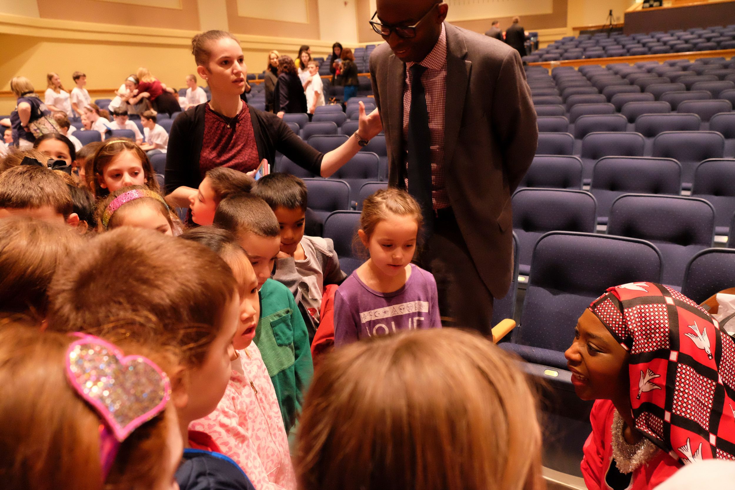 Georgie Badiel, spoke with second graders from School No. 9E while Principal Josh McPherson looks on. WIC advisor Danielle Block is standing to the left of Mr. McPherson