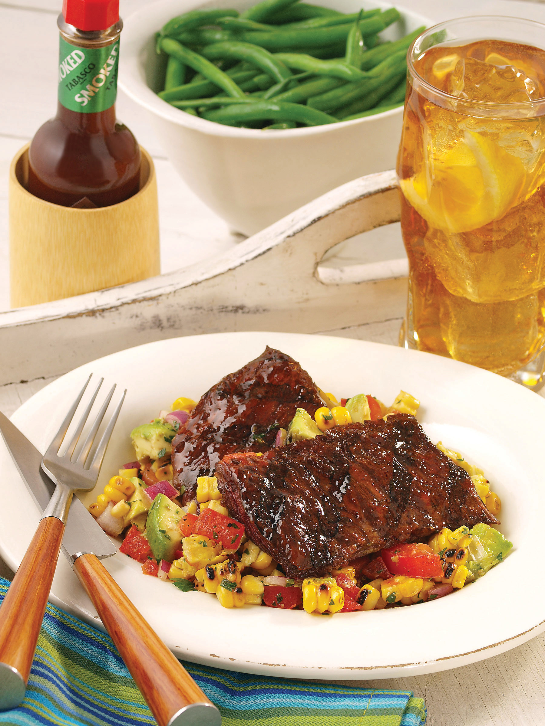 A quick and easy chipotle marinated grilled skirt steak will spice up any gathering. Pair it with a roasted corn salad that embodies the fresh flavors of the season — a mixture of corn, tomato, red onion, basil, and avocado.