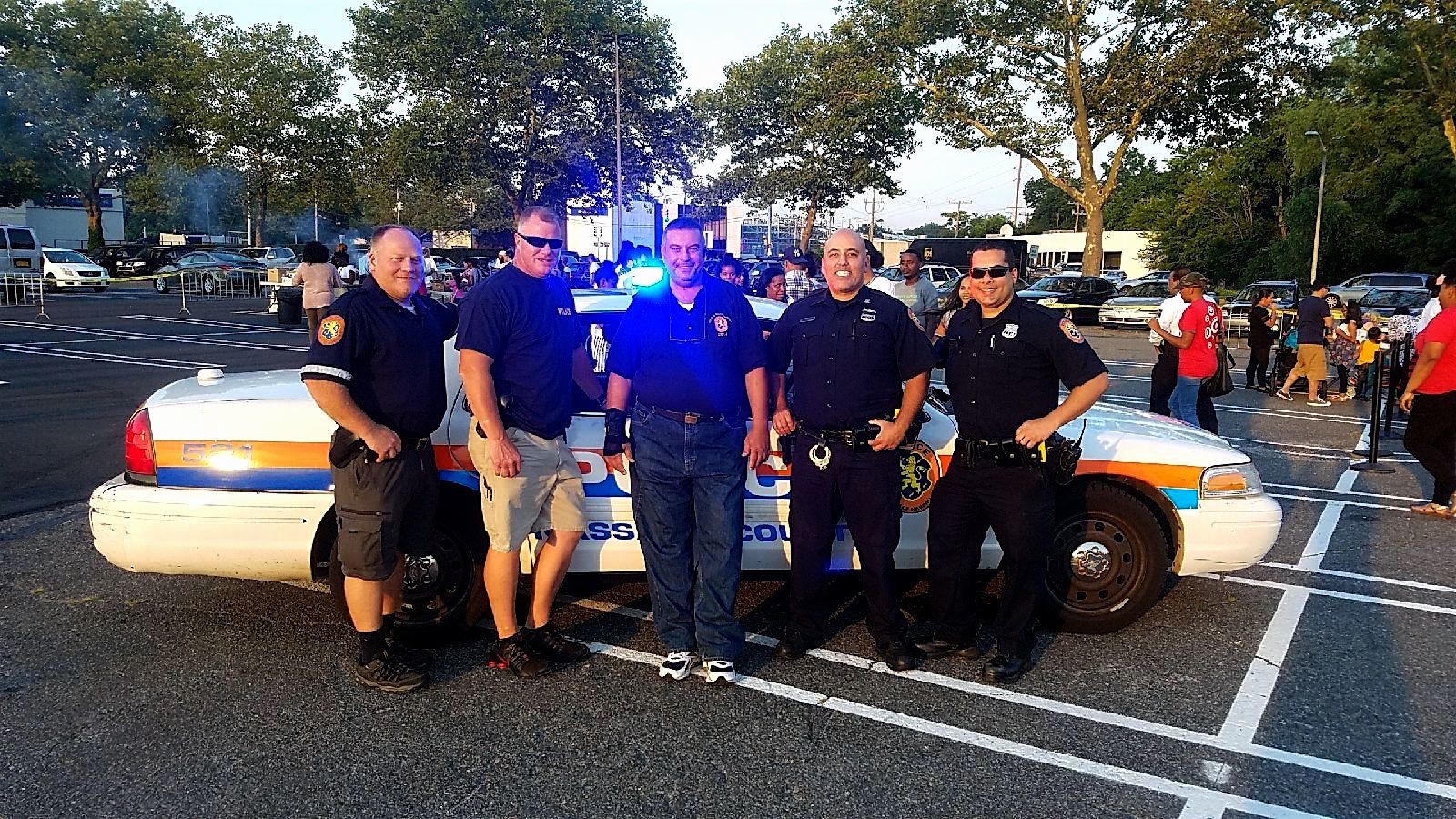 Fifth Precinct officers and community activist Hesham Khafaga, of Franklin Square, center, showed their support for their community at the National Night Out event held at the Green Acres Mall in Valley Stream on Aug. 1.