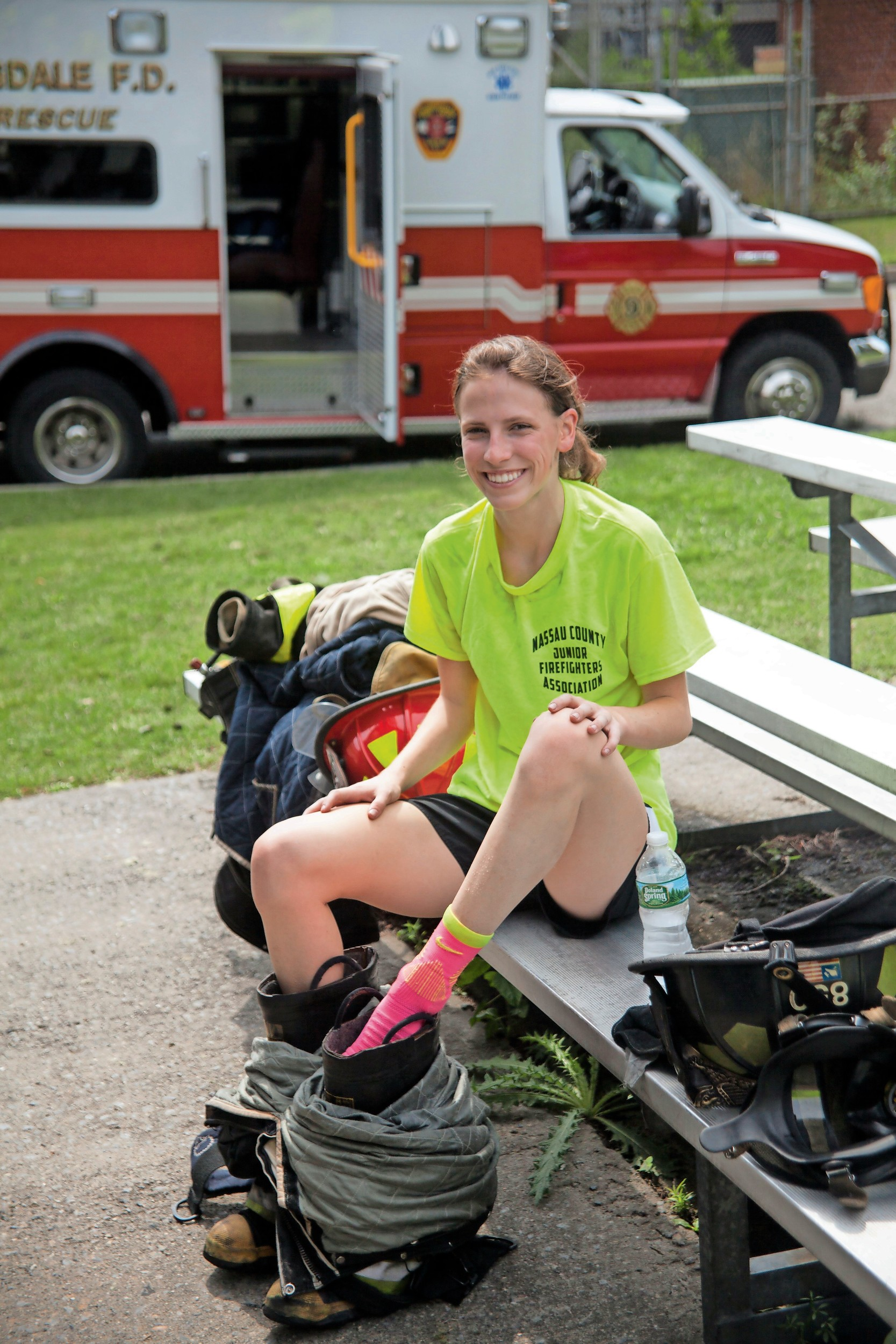 East Norwich junior fighter Colleen Joyce, 16, was relieved to take off all the fire gear after a hot day at the fire camp.
