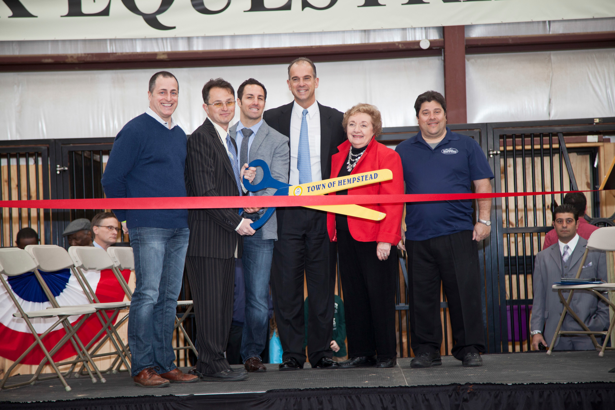 Alex Jacobson, holding scissors, with local politicians and employees of the center at its grand opening on April 20, 2013.