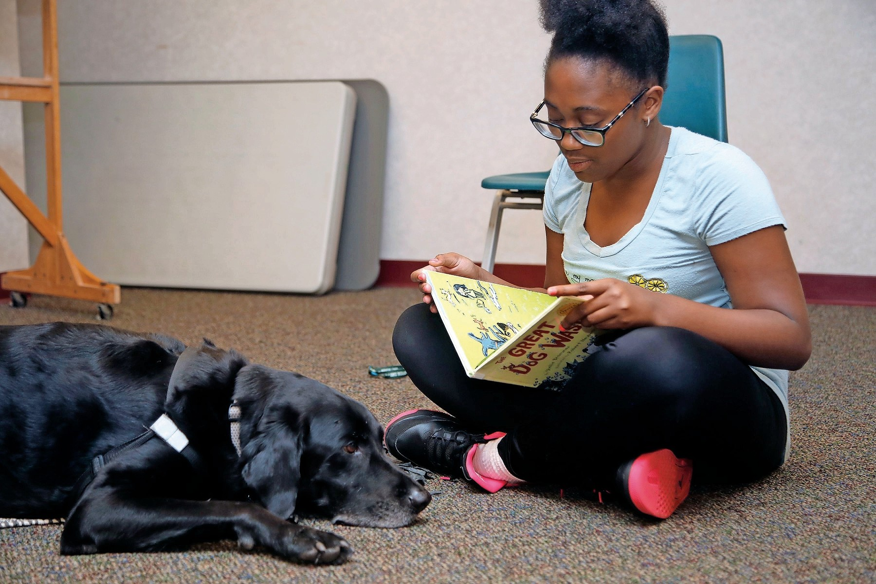 "Kristina Gray, 12, read ""The Great Dog Wash"" to Buddy during the Rockville Centre Library's Reading to Dogs program on Aug. 7."