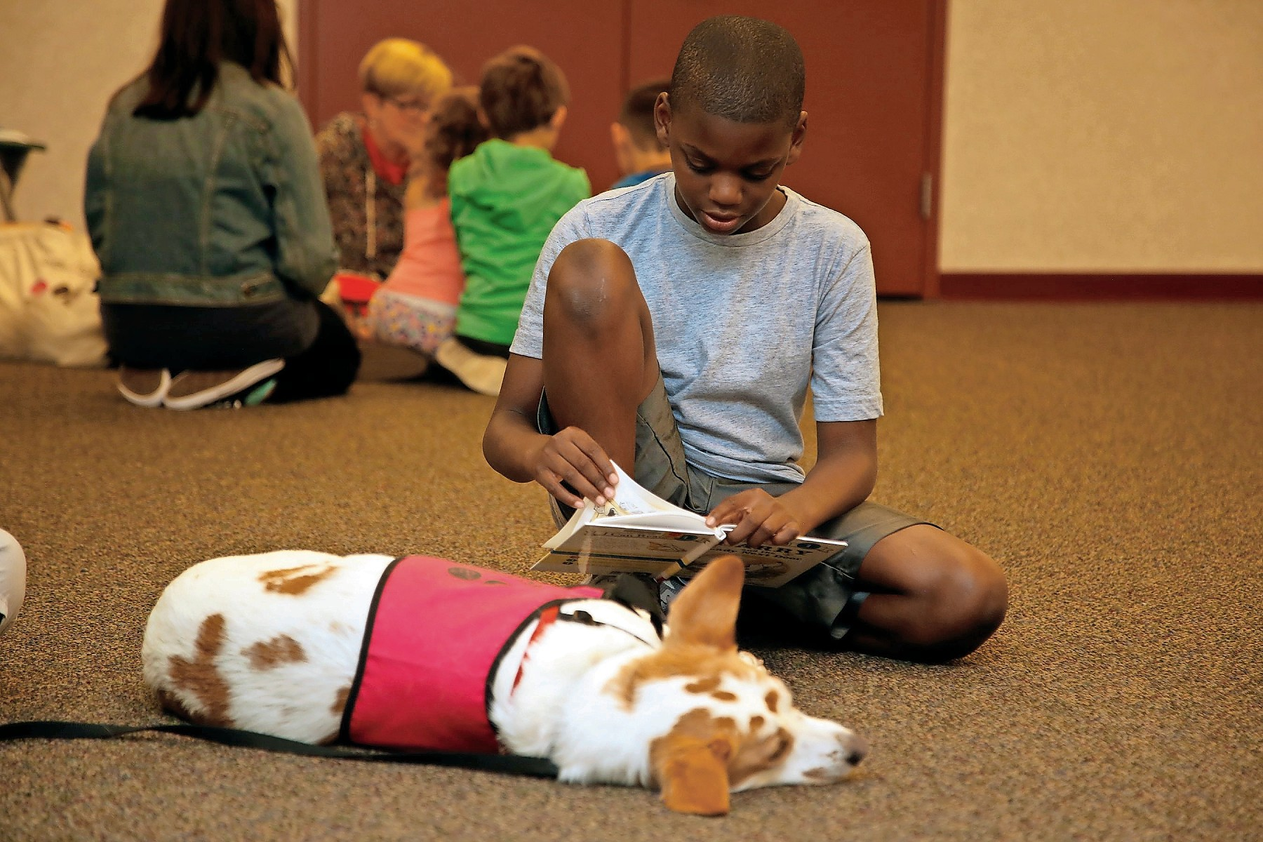 Aaron Stewart, 11, enjoyed a book as his canine friend, Chelsea, listened.