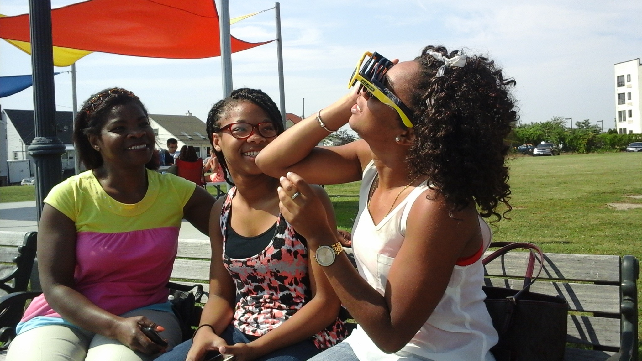 Roosevelt residents Roslind, Amelia and Marian Juste observed the eclipse from a bench in Seabreeze Park.