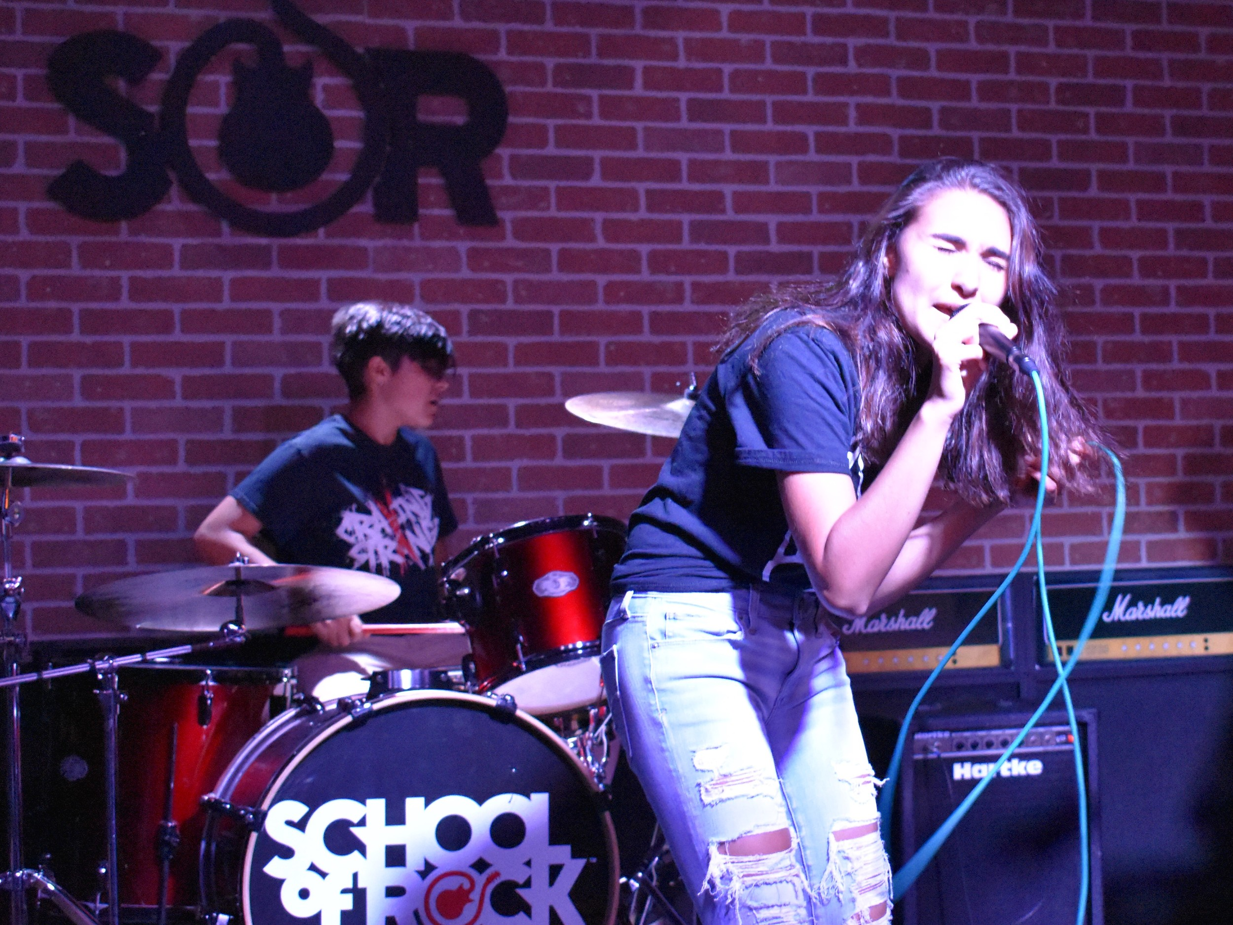 Singer Katie Bacchi, 17, and her sister, Emily, 13, of Rockville Centre, rehearsed with the School of Rock's house band, Trip Wire, last week.