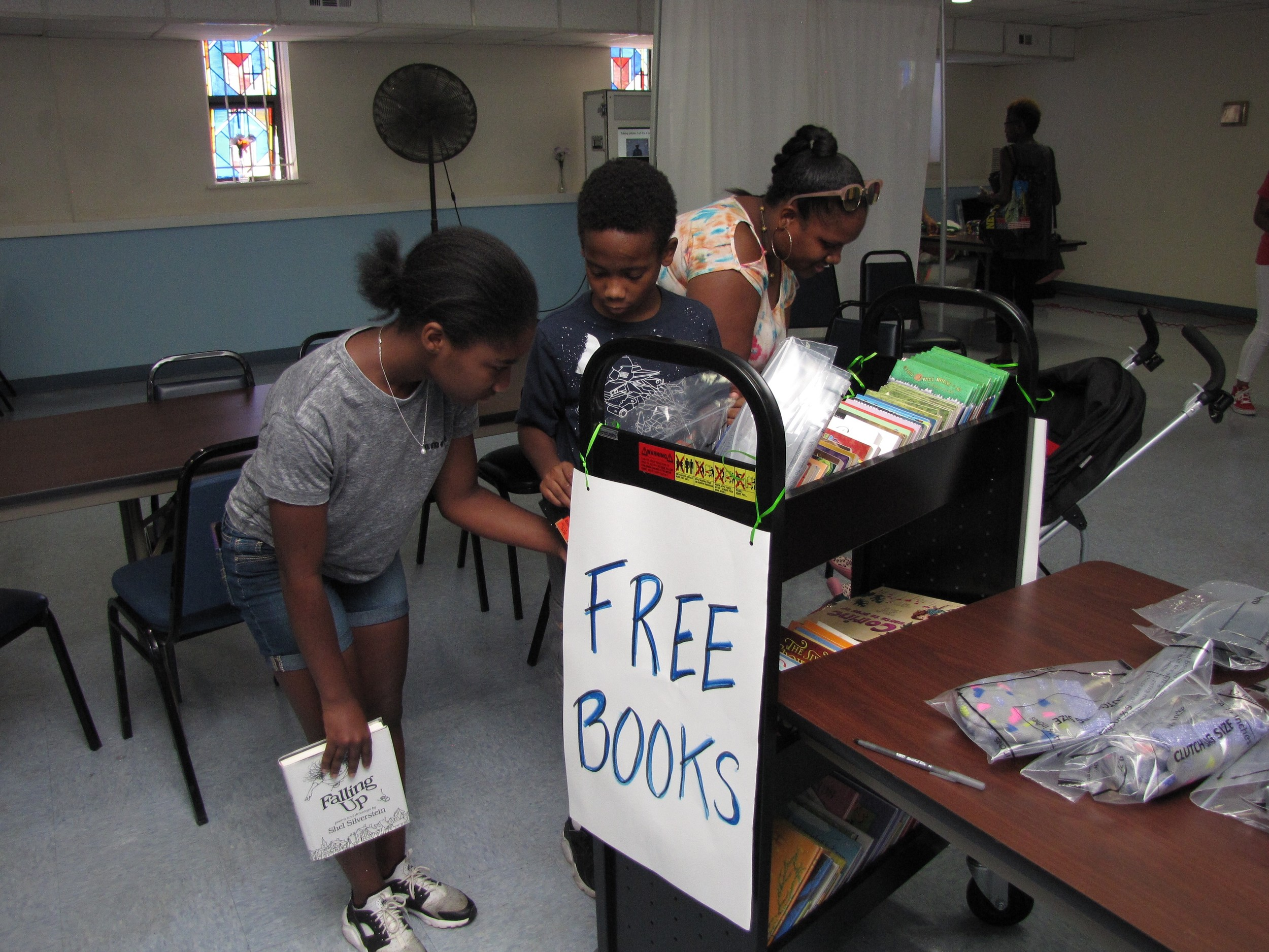 Kamille Thompson, right, browsed through the free books with her son, Dominic Solomon, 10, center, and her niece, Niyah Thompson, 13.
