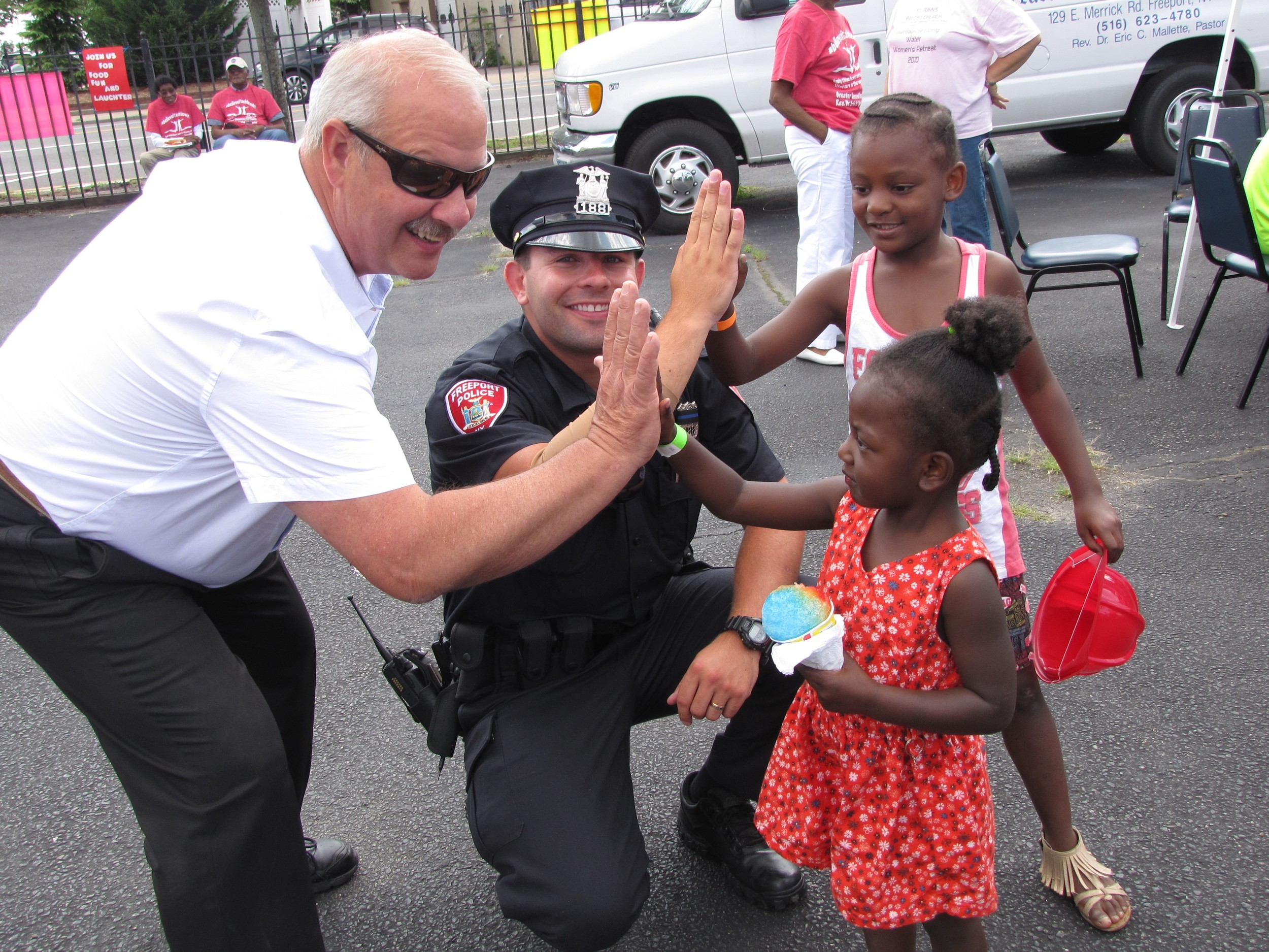 Mayor Robert Kennedy, and Freeport police officer Fred Gutmann greeted Kamyrn Jeter, 7, from New Visions School in Freeport, and Aneessa Hartman, 3 during the ninth annual Community Back-to-School Barbecue at the Greater Second Baptist Church in Freeport on Aug. 26.