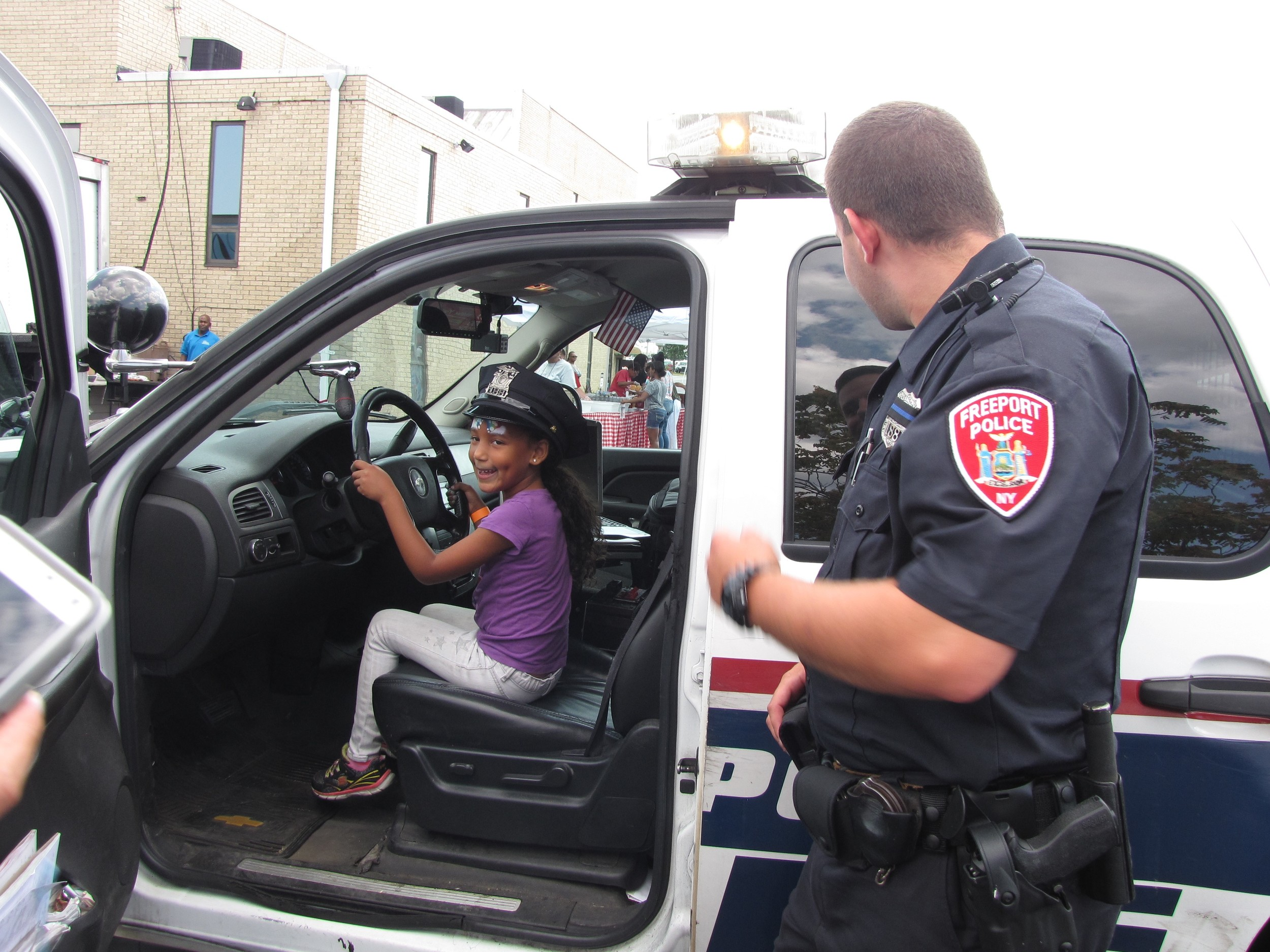 Excited to wear Gutmann's hat, 6-year-old Itzela Vargas sat in the driver's seat of his police cruiser during the back-to-school barbecue.