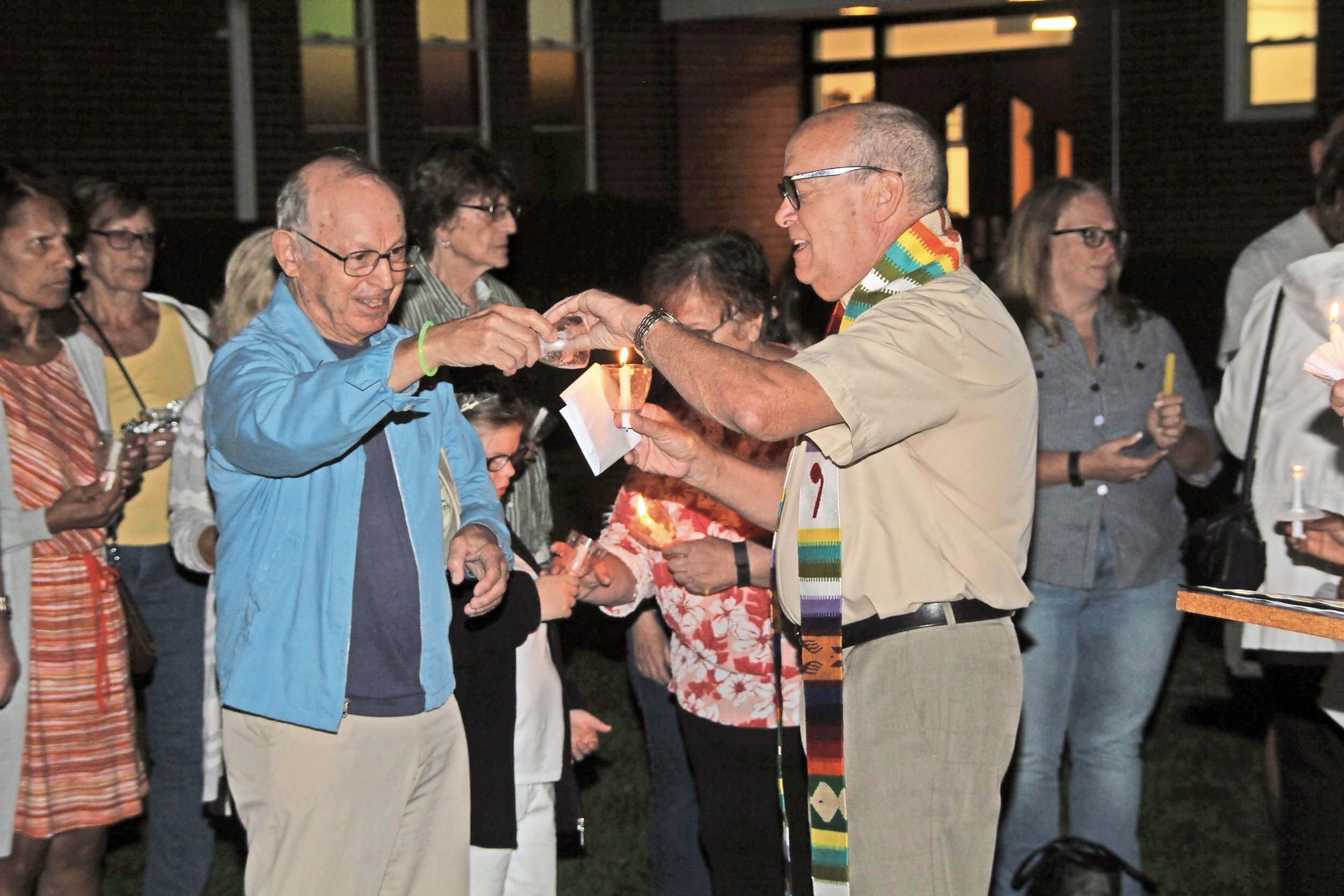 The Rev. Ron Garner, right, pastor of Wantagh Memorial Congregational, lit residents' candles using one flame to show that the community is united.