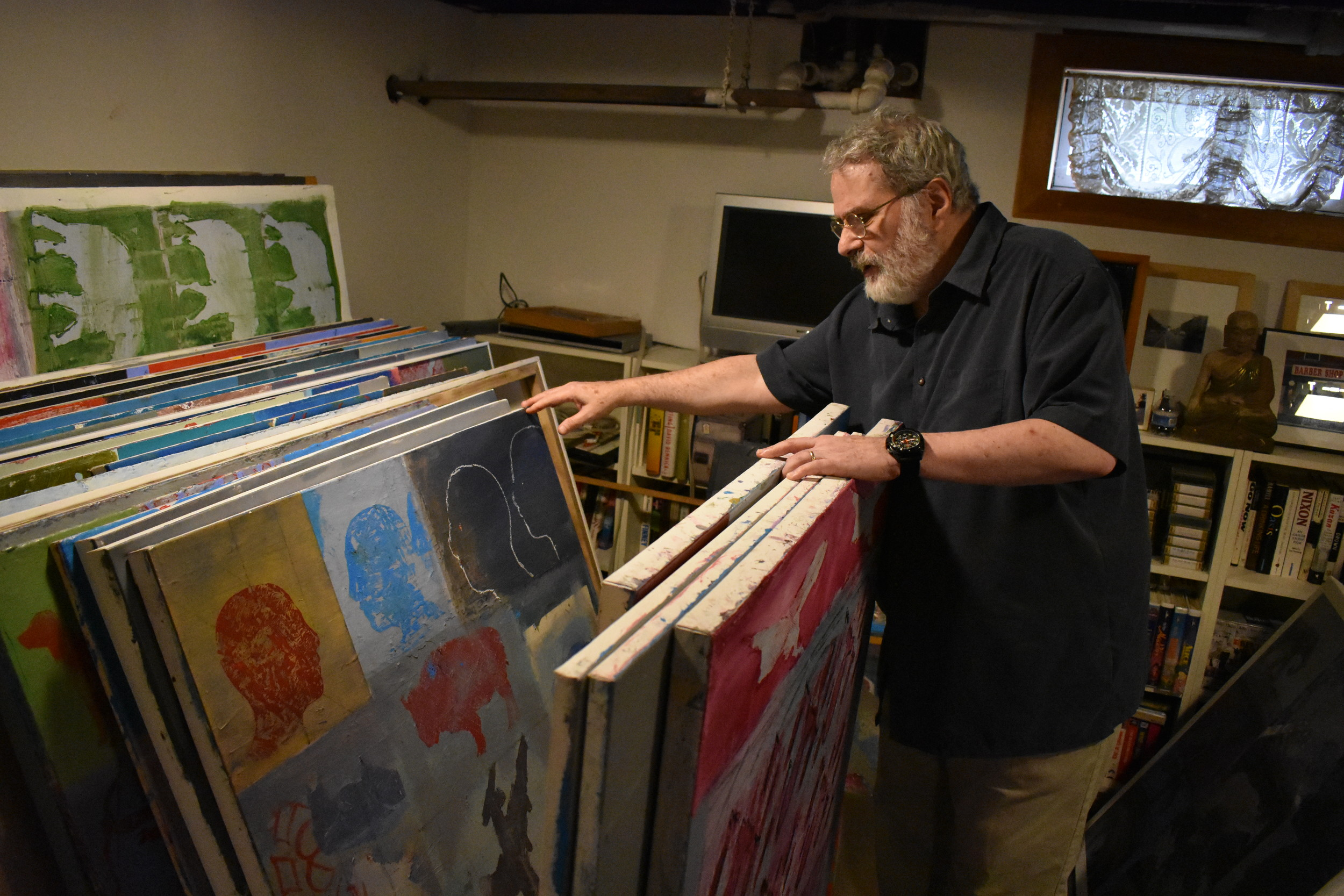 The Vietnam Veteran sifted through the many works in his basement.