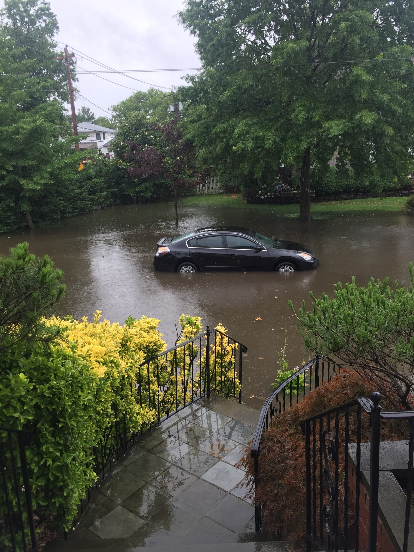 The intersection of Meadow Land and Marbridge Road in Lawrence has flooded for years, residents said. Above, a car stranded after a July rainstorm.
