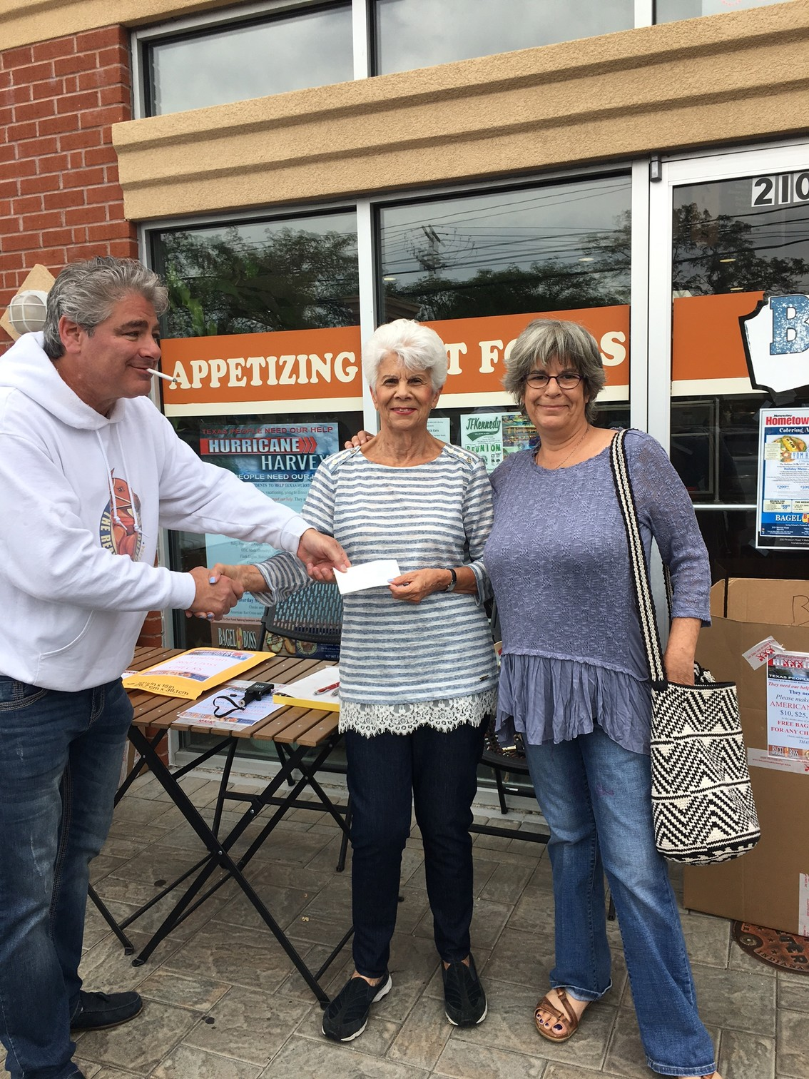 Ron Steiger, left, was one of the organizers of a supply drive for Hurricane Harvey victims on Saturday. Helen Pazer and Robin Gross donated a check for relief efforts.