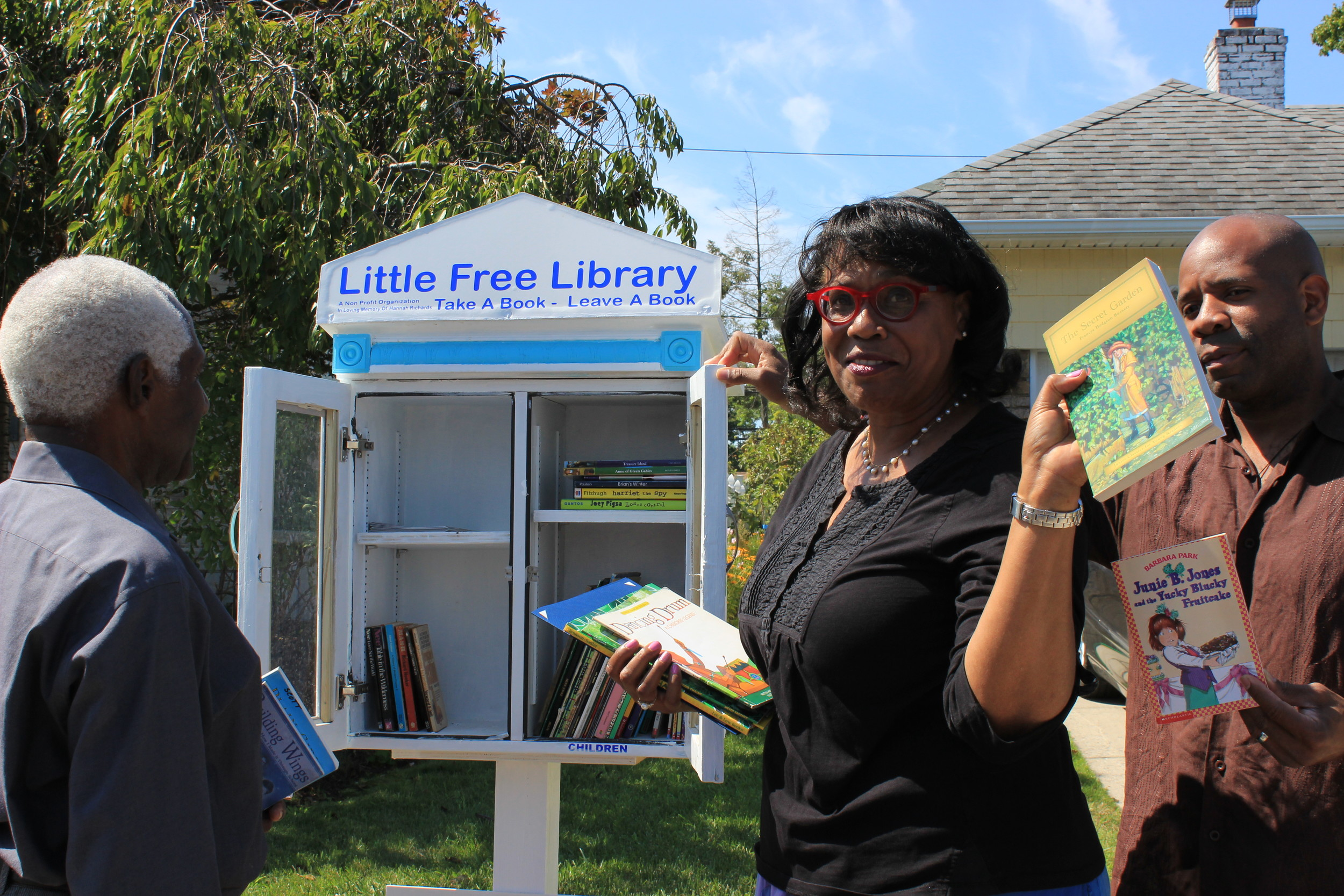 Marcia Morgan, center, worked last fall to create a literacy program called Little Free Library. She put books in the tiny structure, which is in the front yard of her Elmont home. She is joined by her husband, Leonard Morgan, left, and his son, Christopher Morgan, right.