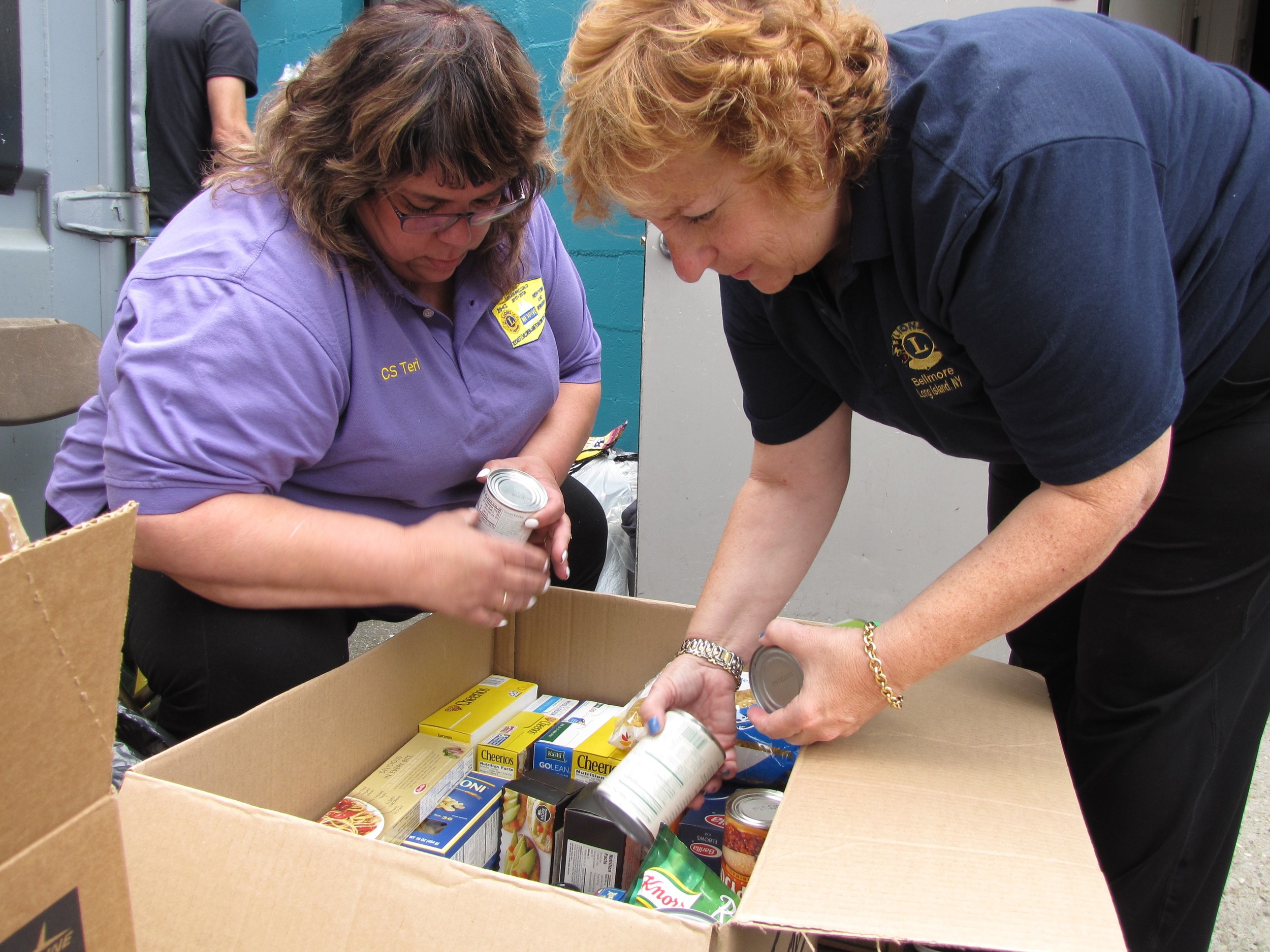 Long Island Lions Teresa Omarie of West Hempstead and Camille Raya of Bellmore sorted through the non-perishable food donations during the Lions Clubs of Long Island Hurricane Harvey emergency relief supply drive on Sept. 2 in Massapequa.