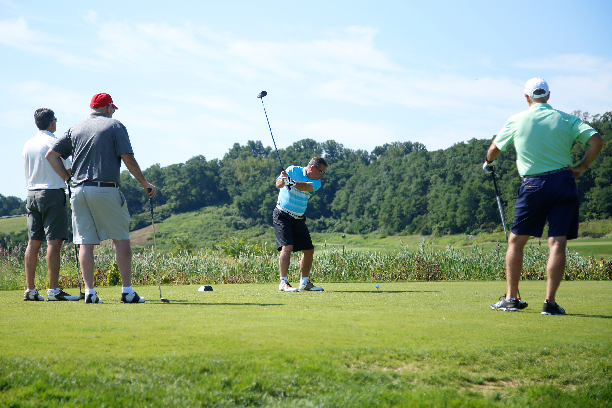 Honoree John Hrvatin, center, takes his stroke as the rest of his friends, Ed Hrvatin, left, Mike Cammarota and Dave Mullane, right, watched. (Right)
