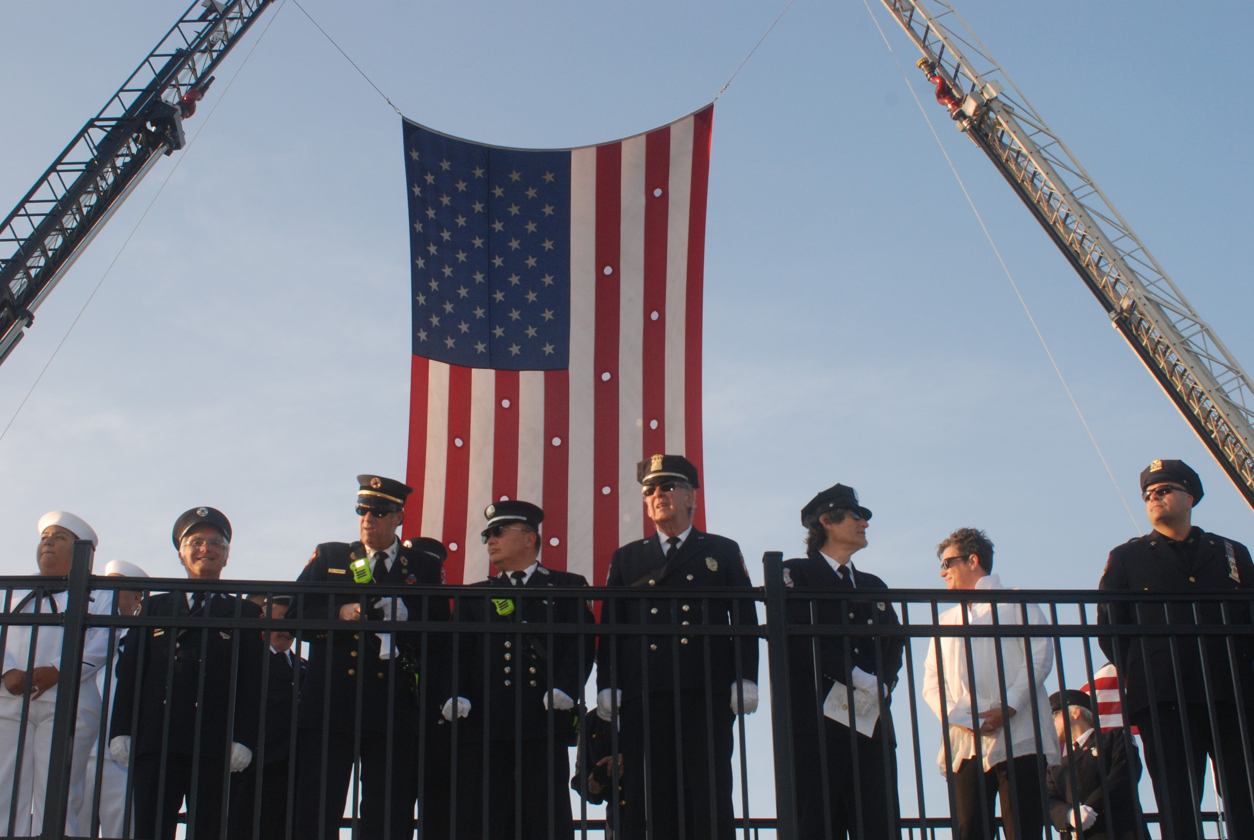 First-responders and members of the military stood atop the town's new 9/11 memorial, with a massive American flag hung behind them.