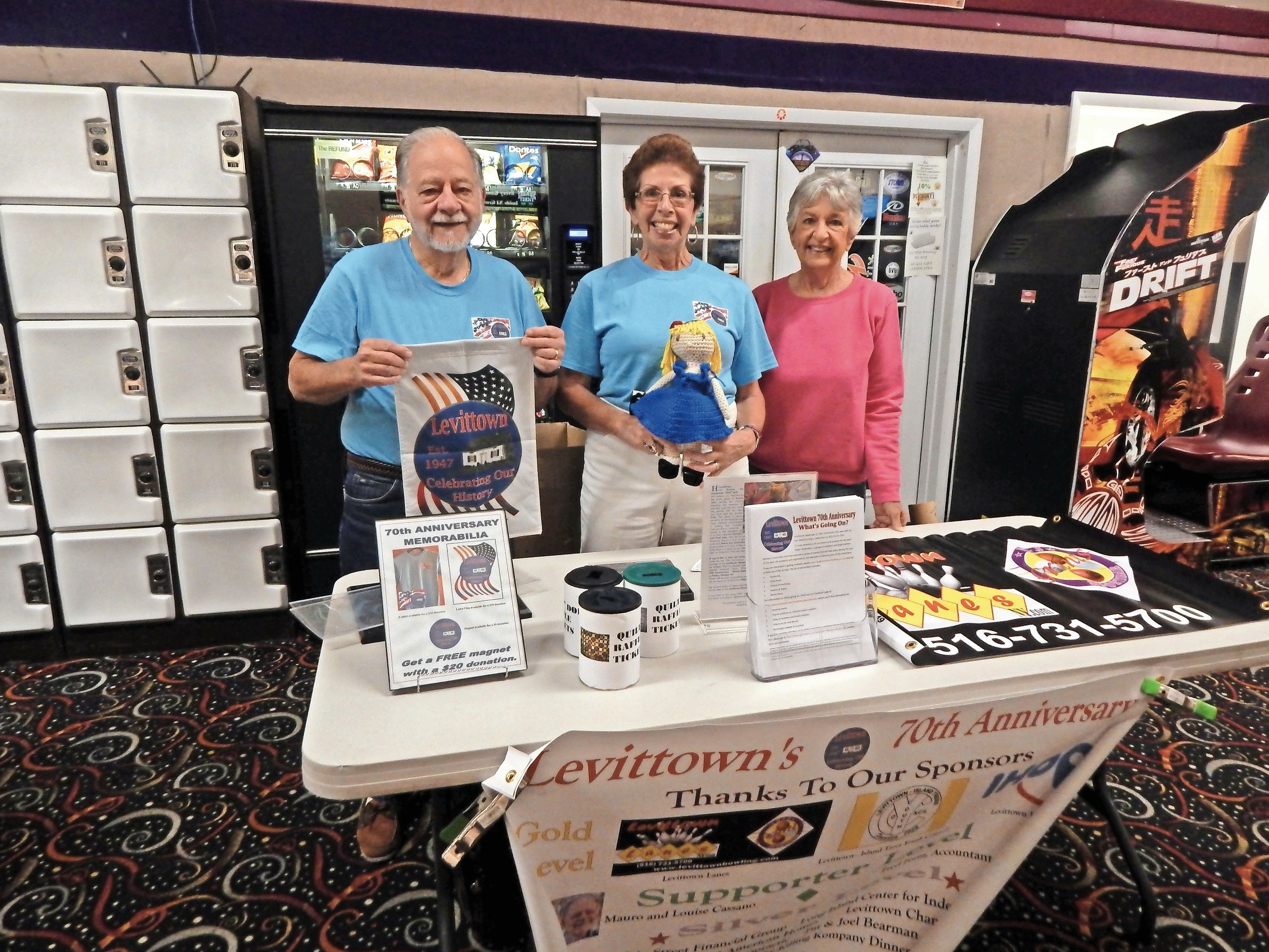 Mauro Cassano, left, Louise Cassano and Betty Johnson sold Levittown 70th anniversary memorabilia.