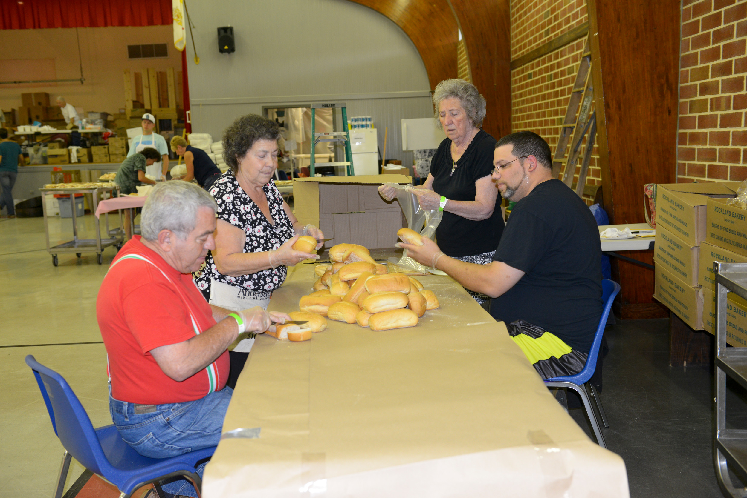 Henry Monteverdi, left, Sylvia Leo, Mayann Guarino and Andy Otero slice bread for sandwhiches at the San Gennarro Feast