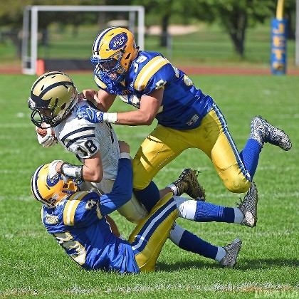 Baldwin's David Garcia, No. 18, was sandwiched between East Meadow's John Grigonis, bottom, and Tyler Love during last Saturday's Conference I football opener.