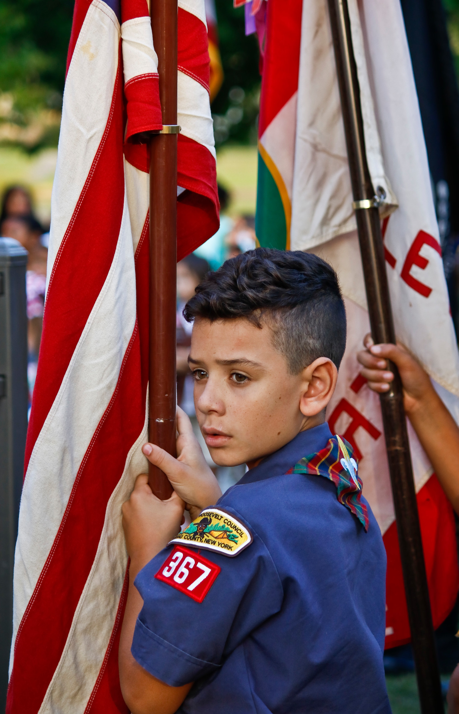 Joining the American Legion, VFW, Girl Scouts and other Boy Scouts, 10 year old Logan Thomson carried the American flag during the presentation of colors and took up his spot as the groups surrounded the memorial at Hendrickson Park.
