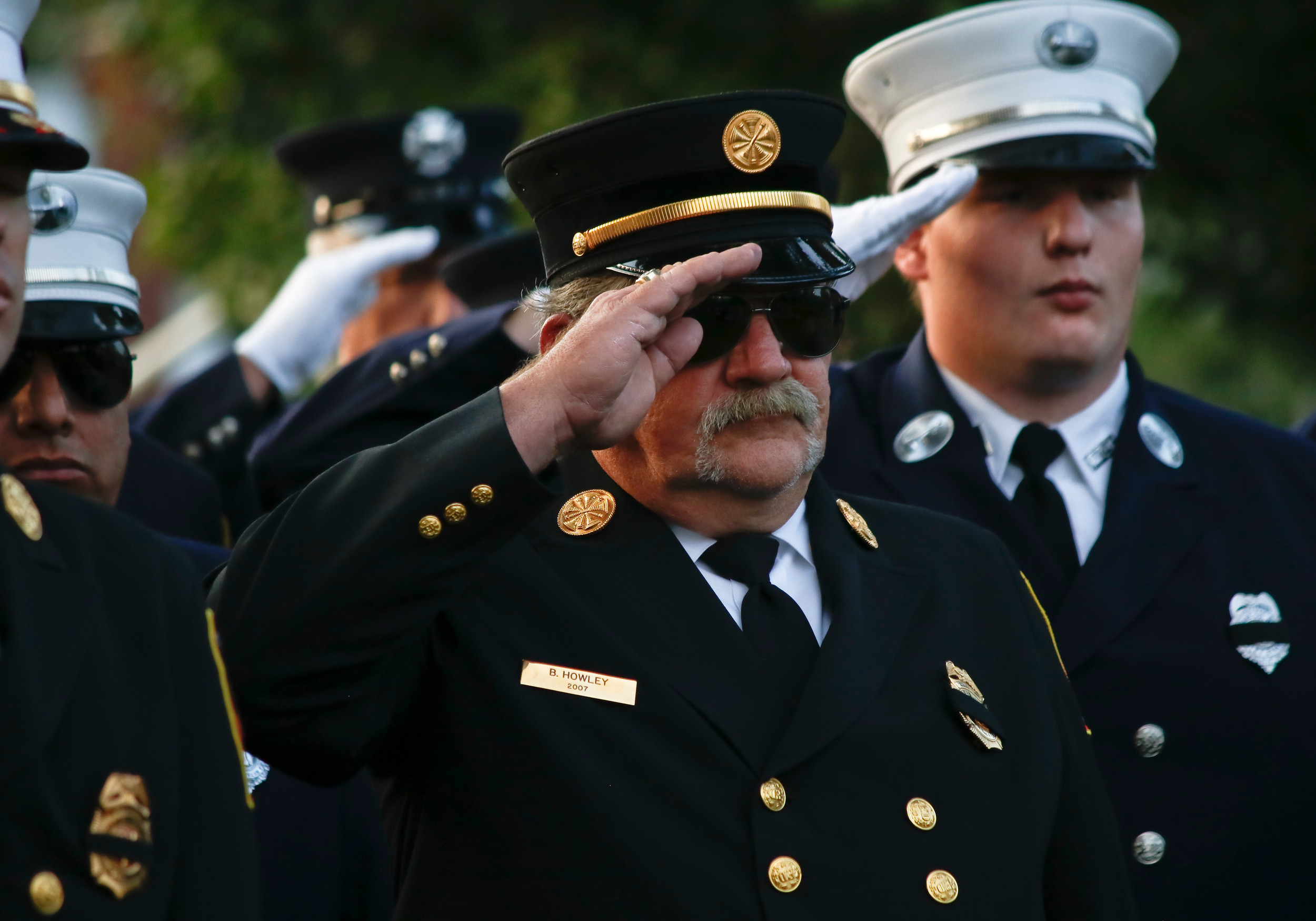 Brian Howley, center, along with the rest of the fire department, saluted during the playing of taps.