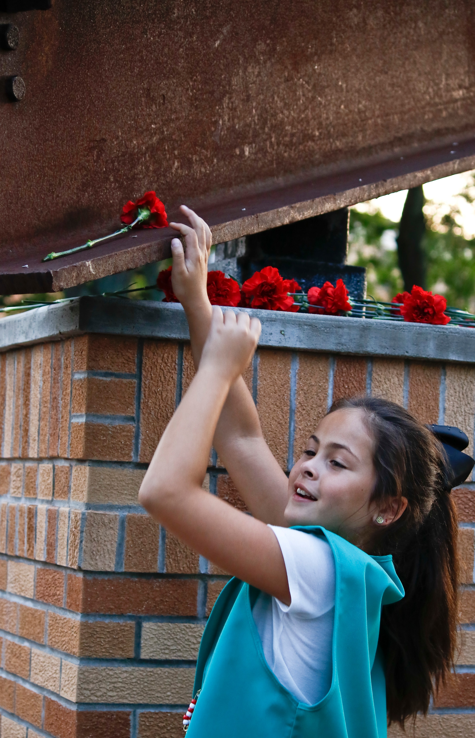 After the conclusion of the ceremony, attendees placed flowers on and around the steel beam from the World Trade Center, which has been in Valley Stream since 2011. Jessica Dyer, 9, from Girl Scout troop 2051 placed her carnation on the beam.