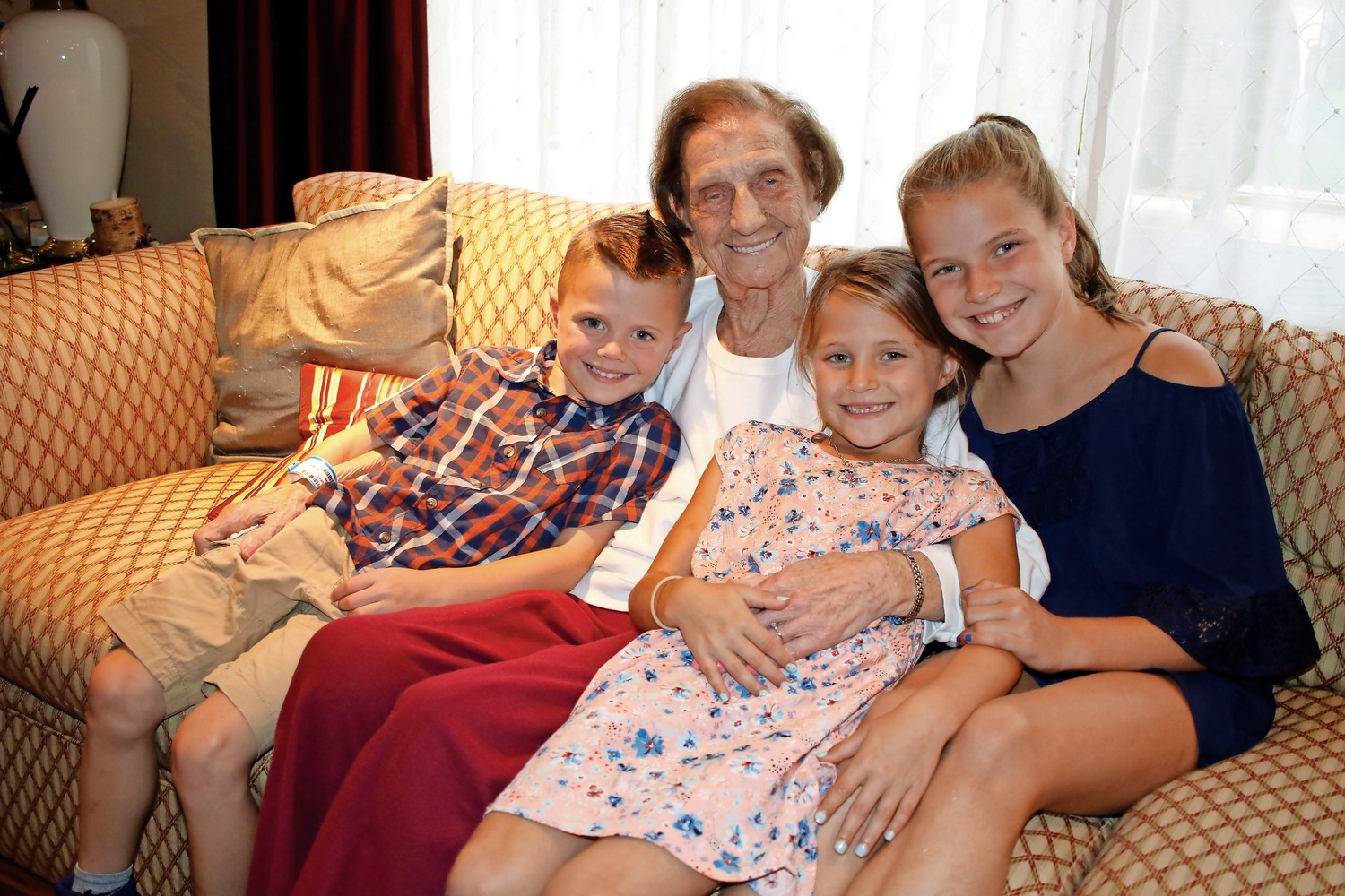 Jack, Allie and Lucy Younghans nestled around their great-grandmother, Mary Fennessy.