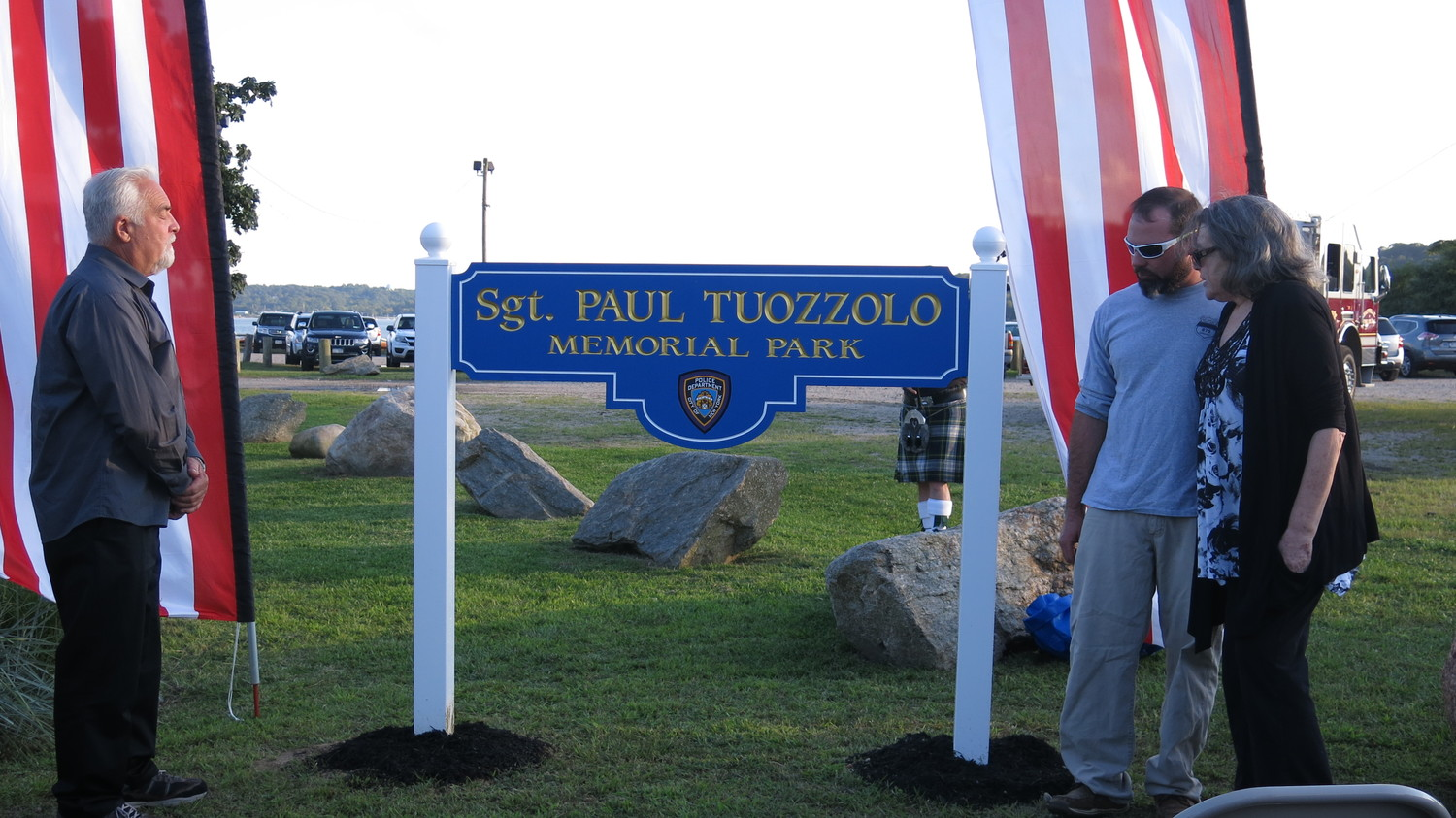 Sgt. Paul Tuozzolo's father, Peter, far left, his brother, Peter, and his mother, Denise, helped unveil the sign at West Harbor Beach that honors Paul, a 19-year veteran of the NYPD who was killed in the line of duty.