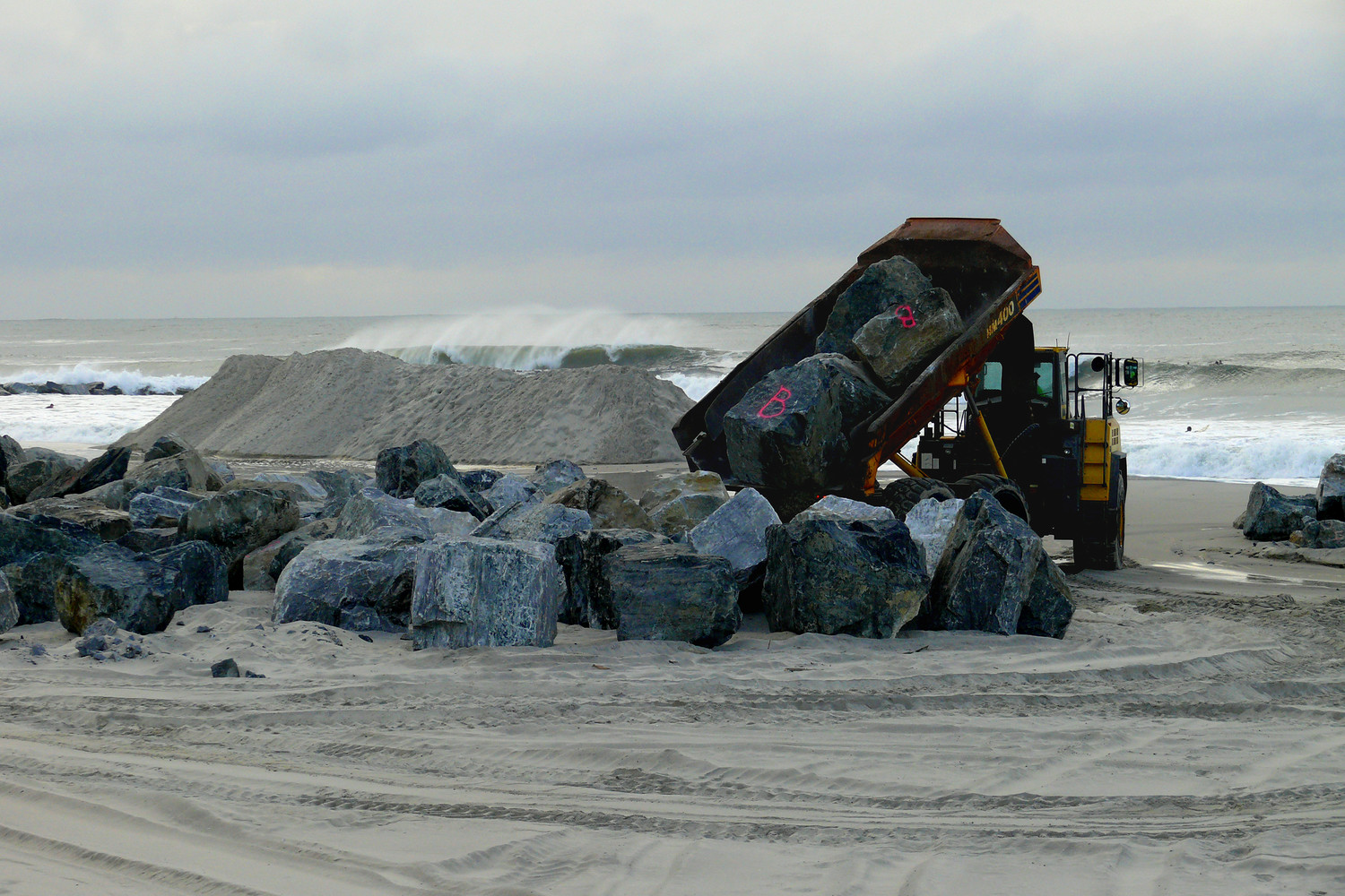 Long Beach's public works crews cleared storm drains and moved sand and boulders along the beach to close off and secure openings in between dunes and along the boardwalk ahead of the storm.