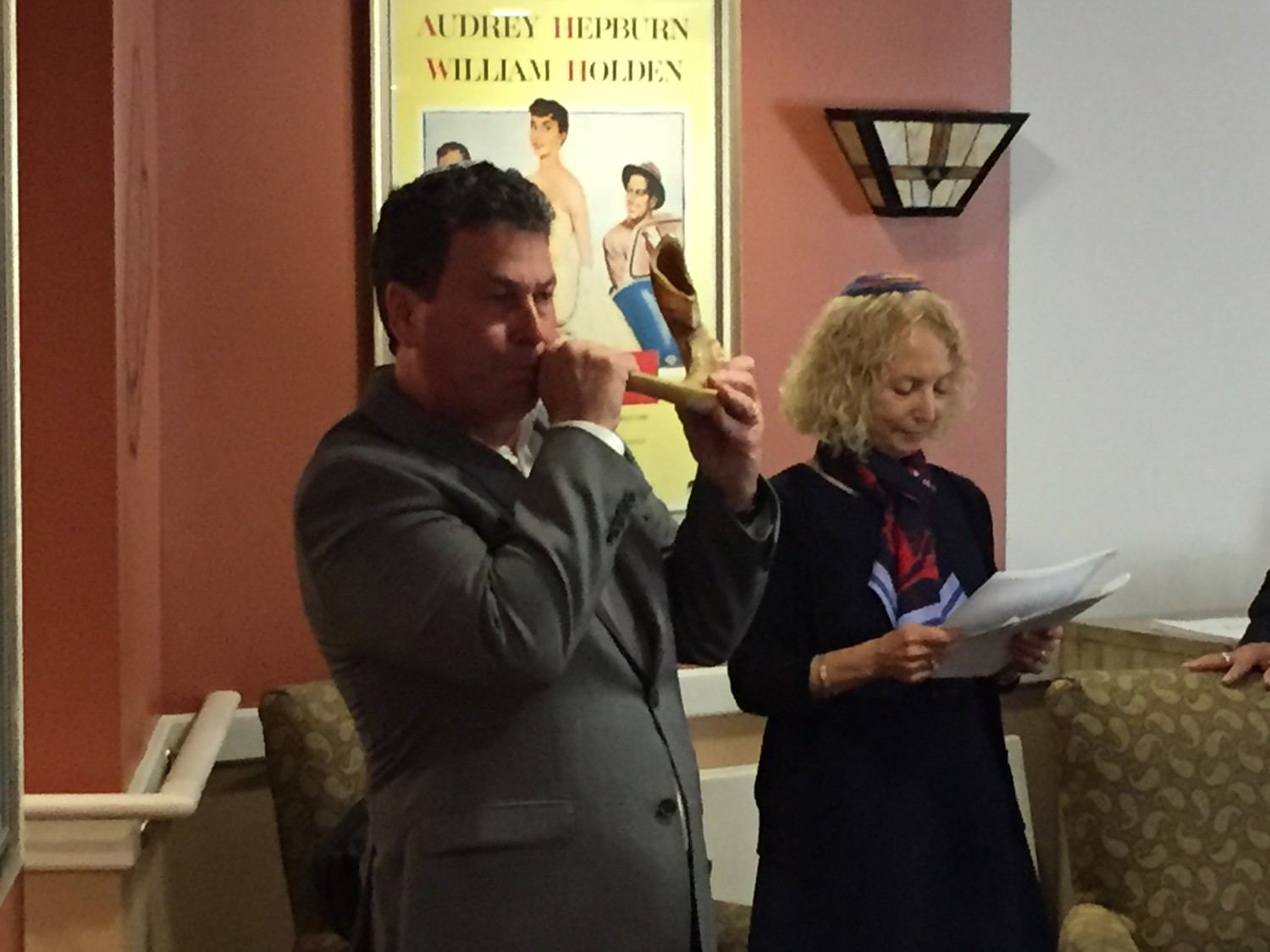 Scott Schnee, with Louise Skolnik, right, blew the shofar, a traditional musical horn.