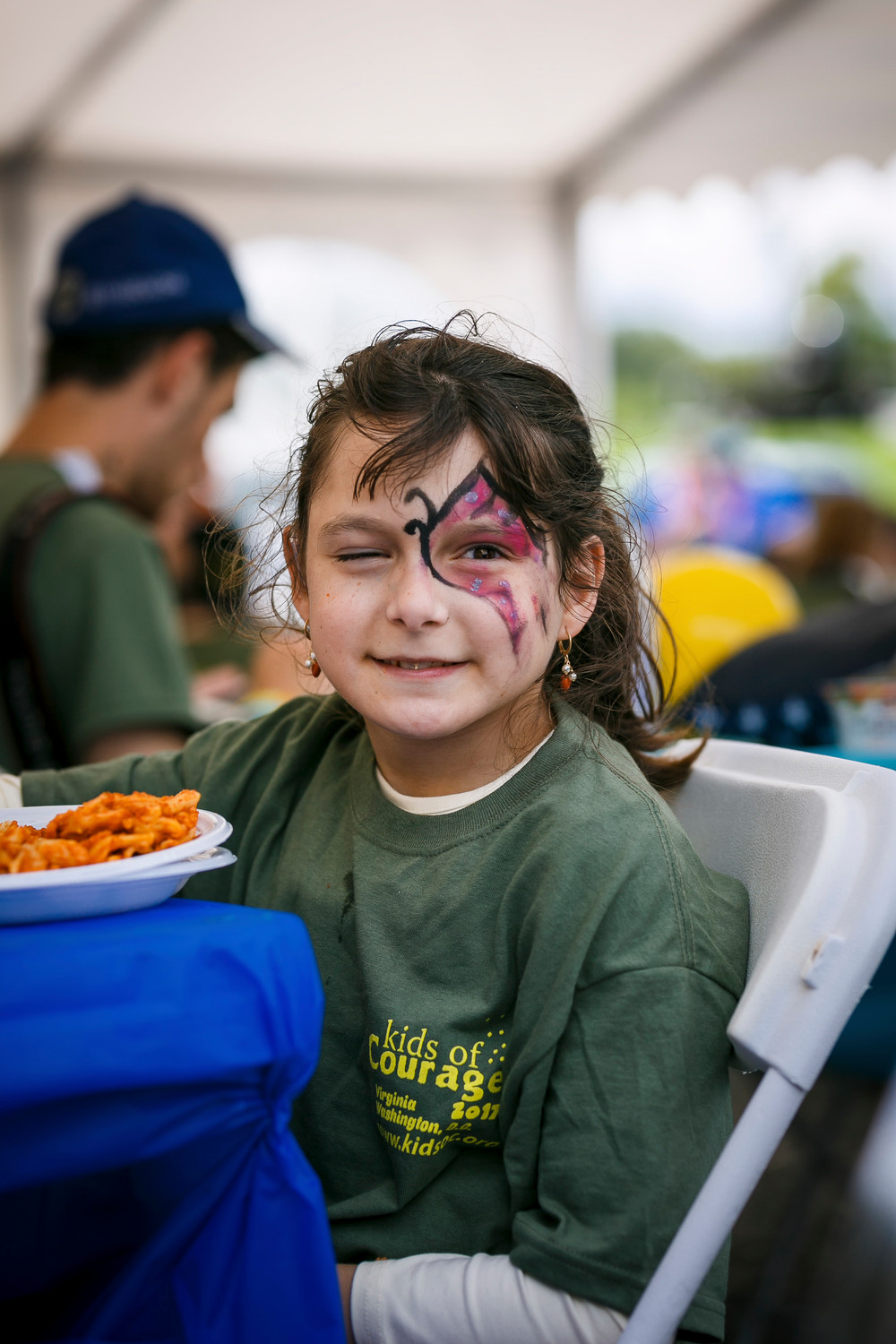 Brooklyn resident Faigy, one of the Kids of Courage campers, relaxed with a meal after having one side of her face painted.