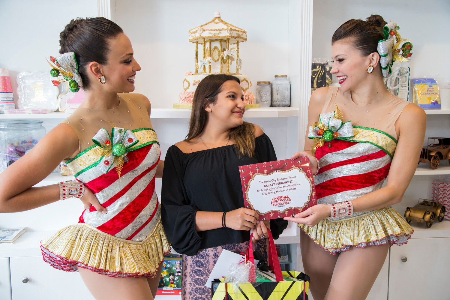 Eleni Gavalas, left, and Courtney Rottenberger, right, gave Fernandez a certificate and a gift bag of Rockettes merchandise.