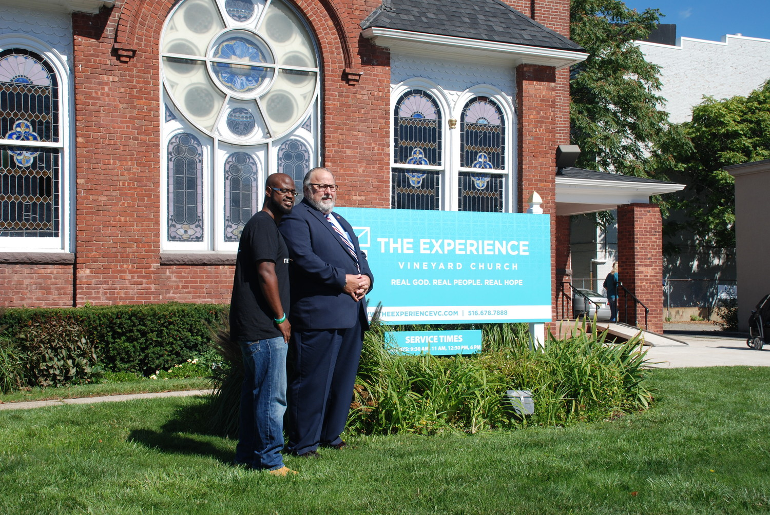 The Rev. Ray Longwood and Mayor Francis X. Murray posed by the new Experience Vineyard Church sign.