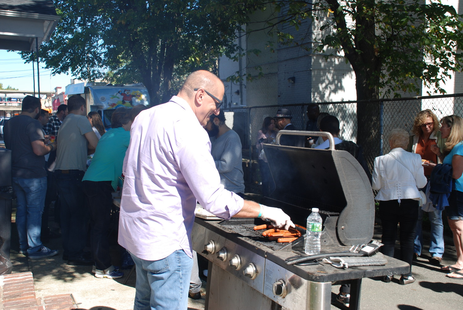 Peter LaRocco, of the Vineyard's prayer ministry, flips hot dogs for the re-launch party-goers.