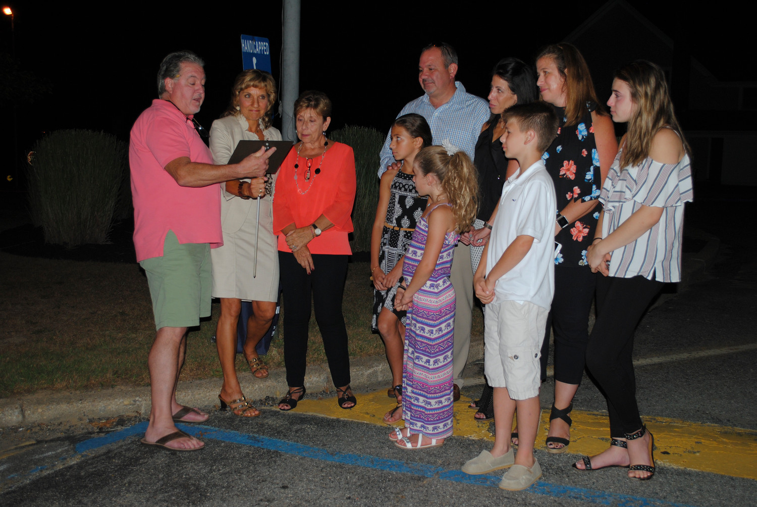 Board trustee David Huggins, left, and Gail Nedbor-Gross, read and presented the plaque for Frank Bouza to his widow, Elizabeth; son and 