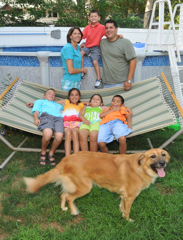 Officer Wayne Resnick, pictured at his home in North Merrick in 2011, with his wife, Patricia, and their youngest son, Daniel, top. Below, from left, were their other children, Benjamin, Nadya, Anya and James.