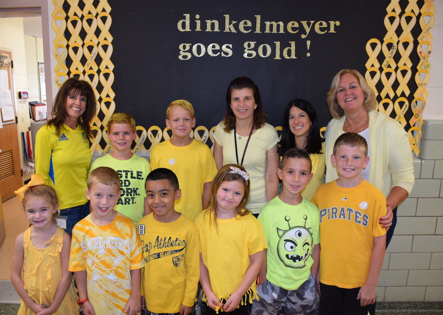John G. Dinkelmeyer Elementary School Principal Faith Skelos, standing right, was joined by students and teachers who wore gold to school on Sept. 29 in support of childhood cancer awareness.