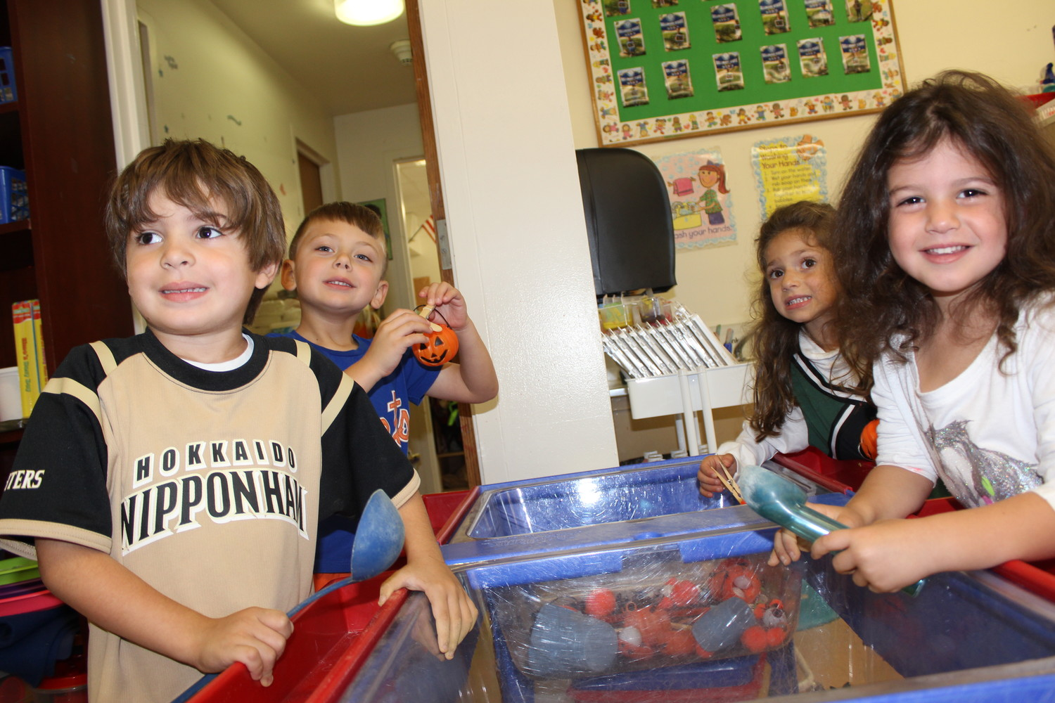 Right: Pre-kindergarten students engaged in a sensory activity to strengthen their fingers and teach them the motor skills necessary for writing.