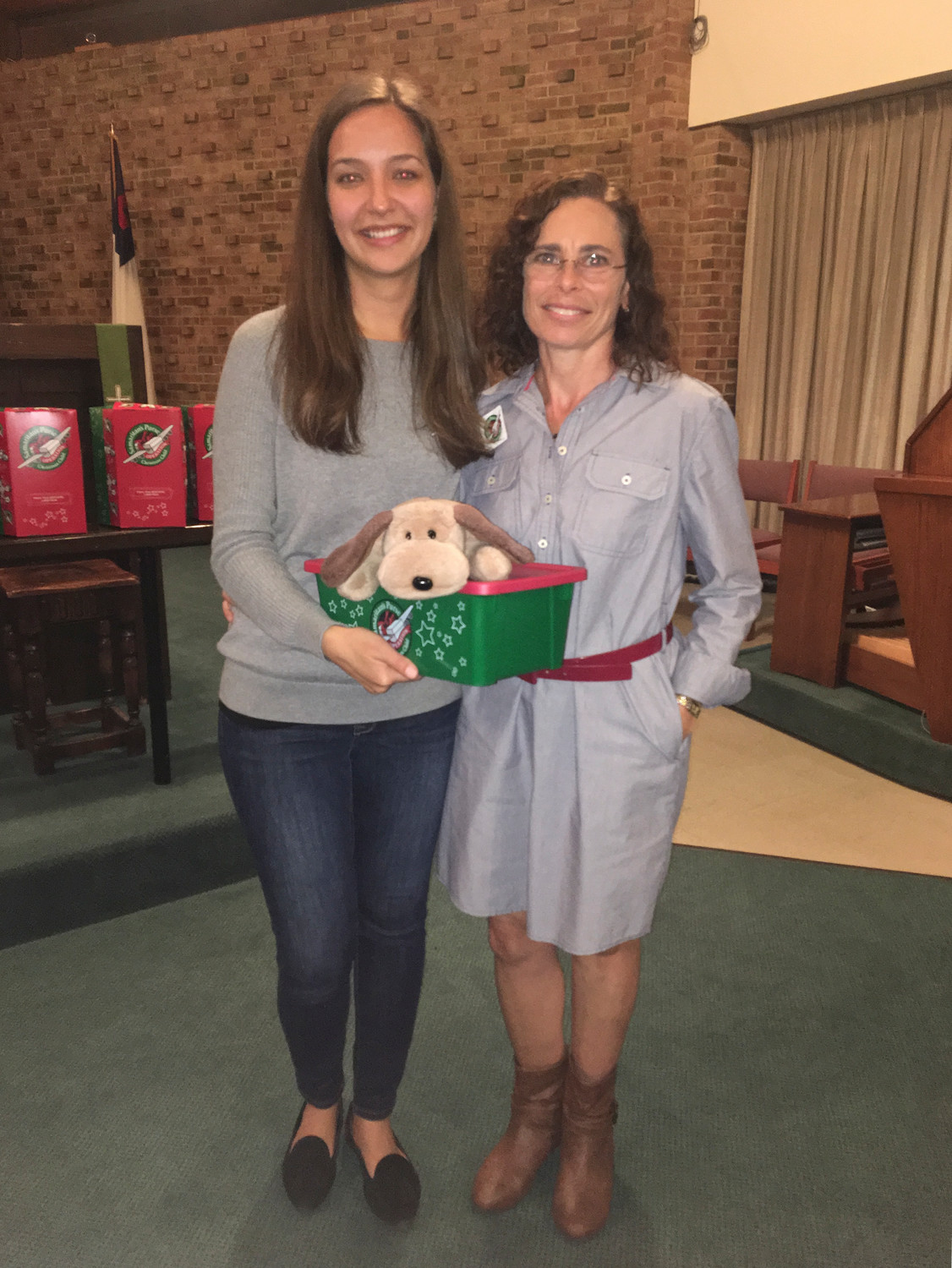 Yulia Shubina, left, and Bonnie Watkins pose with the shoebox Shubina received 16 years ago.