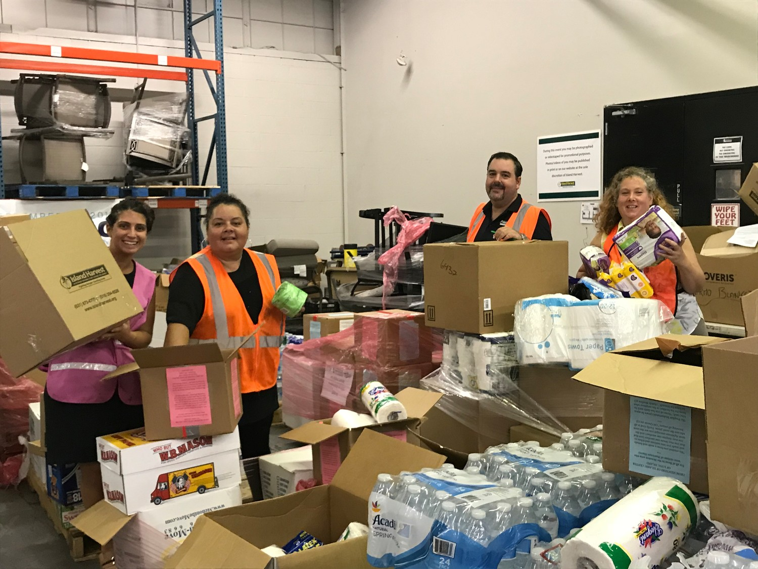 Island Harvest Food Bank employees Elizabeth Notarbartolo, far left, Migdalia Otero, Jeremy Waite and Hillary Hess sorted and packed donated goods on Sept. 27 to be shipped to Puerto Rico.