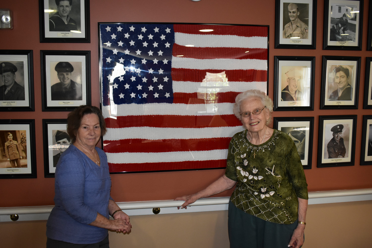 Gloria Rodriguez, left, and Kathryn Chalavoutis, residents at Maple Pointe Assisted Living in Rockville Centre, spent a few months crocheting the American flag that now hangs in a room dedicated to veterans on the center's second floor.