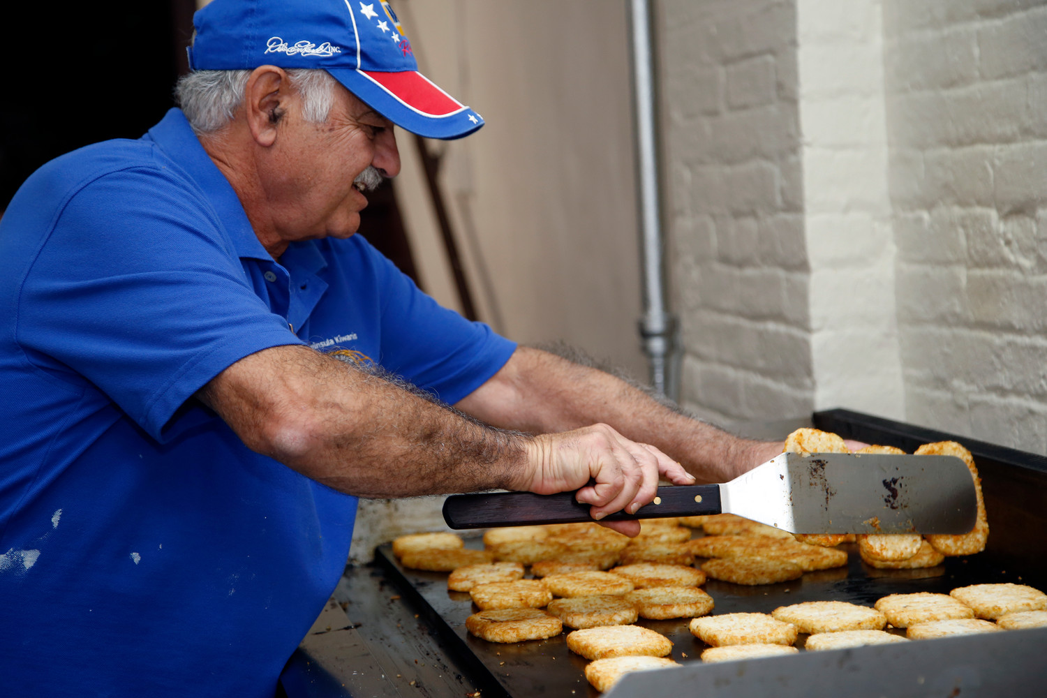 Peninsula Kiwanis member Frank Trabella helped to ensure that the hash browns were evenly browned at the club's annual Christmas Dream Pancake Breakfast on Oct. 1.