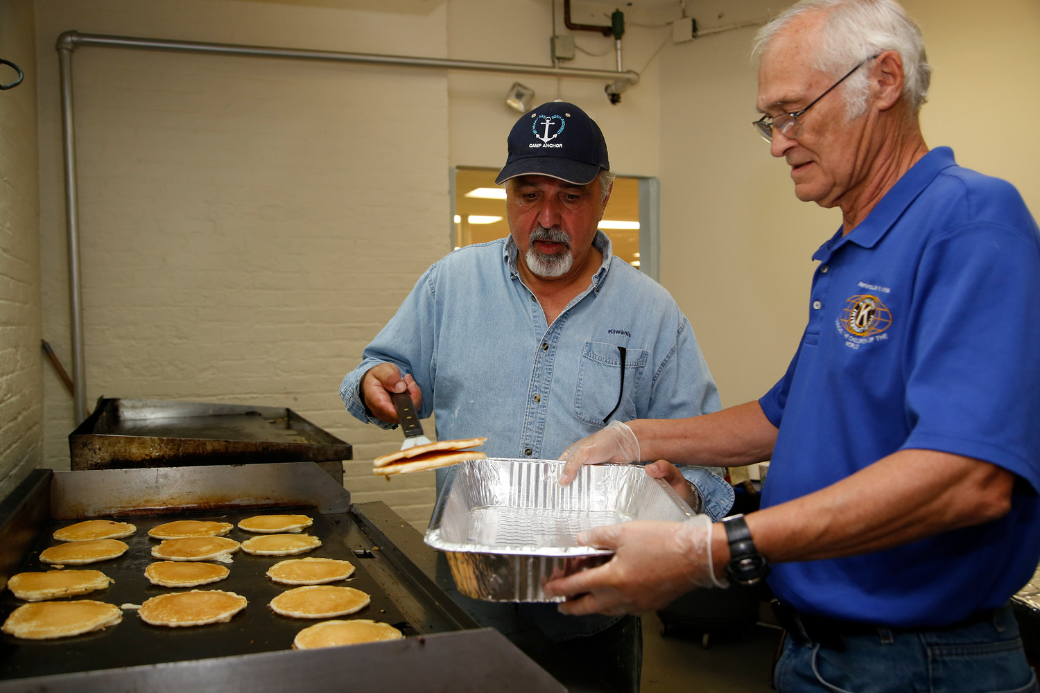 Dominick Curra loaded a tray of pancakes for Dennis Brining to serve at the Christmas Dream breakfast.